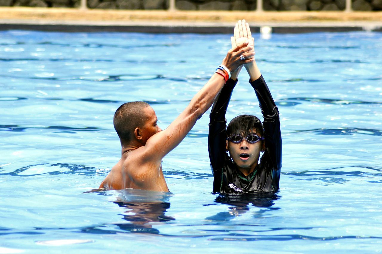 a teenager gets swimming lessons from a swimming coach Boys Childhood Coach Learn Learning Leisure Activity Outdoors People Real People Shirtless Swimming Swimming Pool Teach Teacher Teen Teenager Two People Water Young Youth