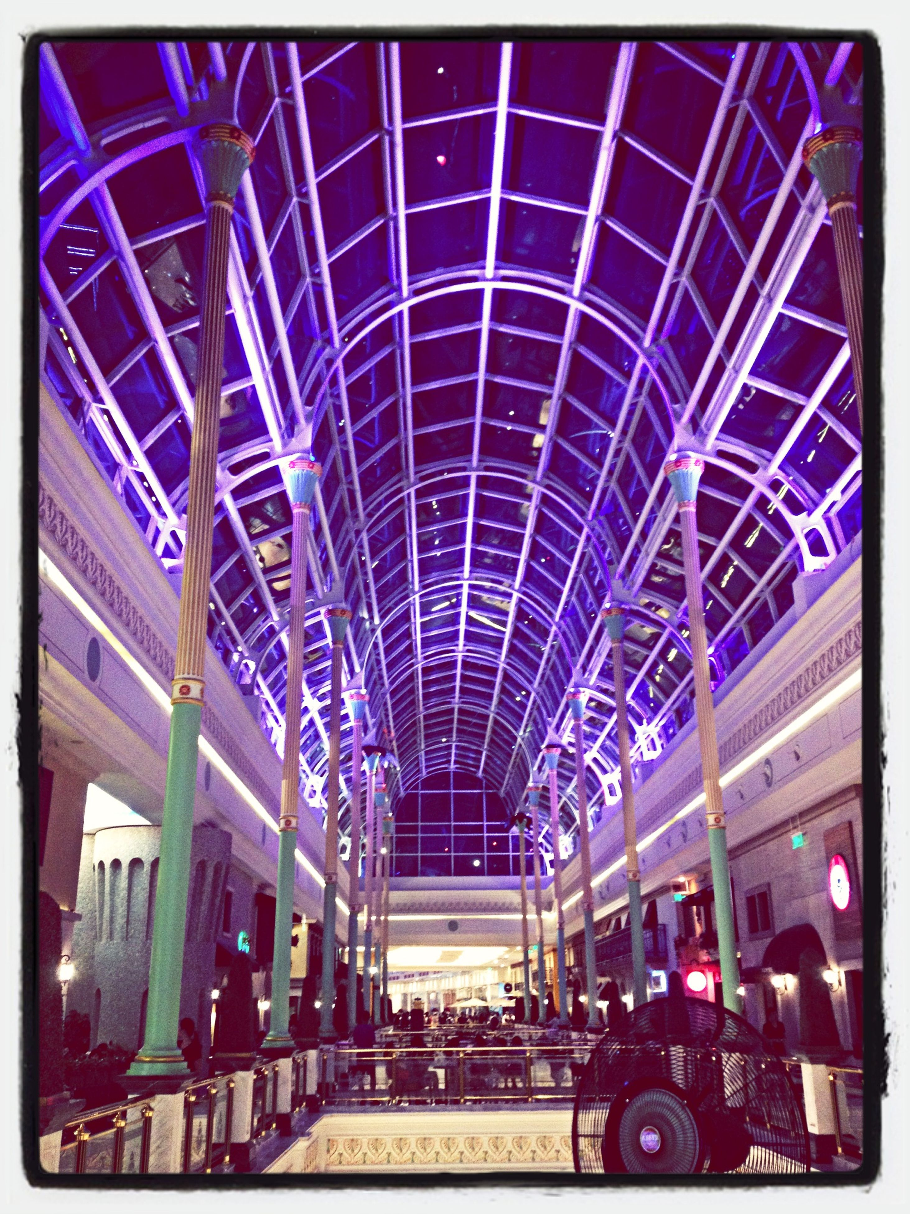 transfer print, architecture, built structure, auto post production filter, low angle view, building exterior, blue, city, illuminated, modern, incidental people, indoors, city life, ceiling, shopping mall, arts culture and entertainment, large group of people, travel destinations, amusement park, glass - material