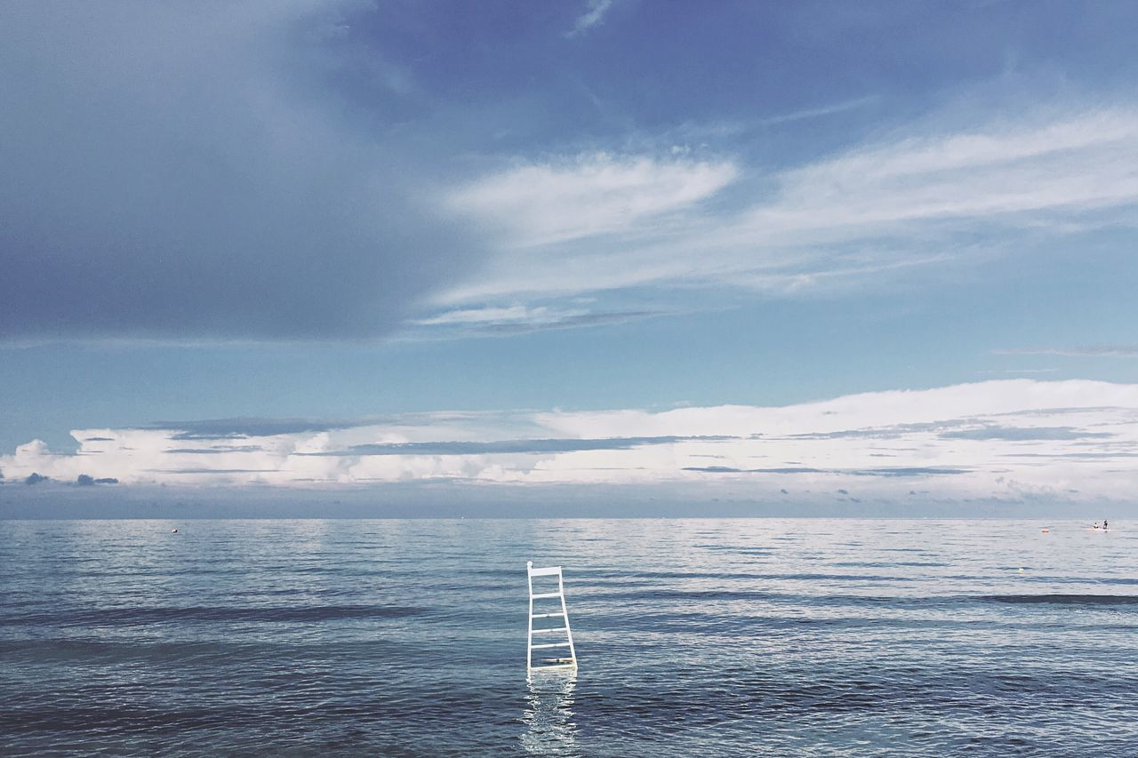 Abandoned Lifeguard Chair In Sea Against Cloudy Sky