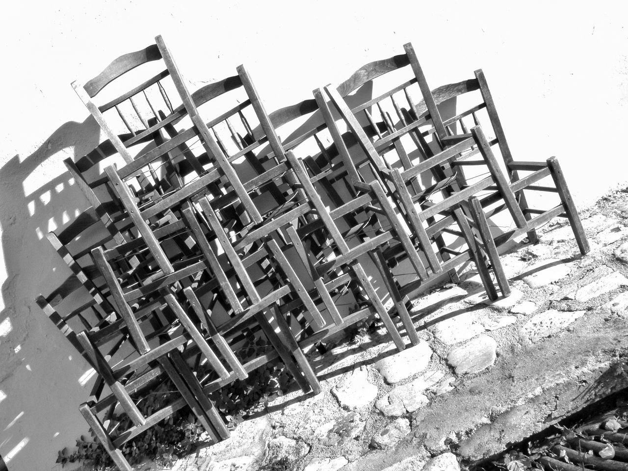 Stack Of Abandoned Chairs On Sidewalk Against Wall