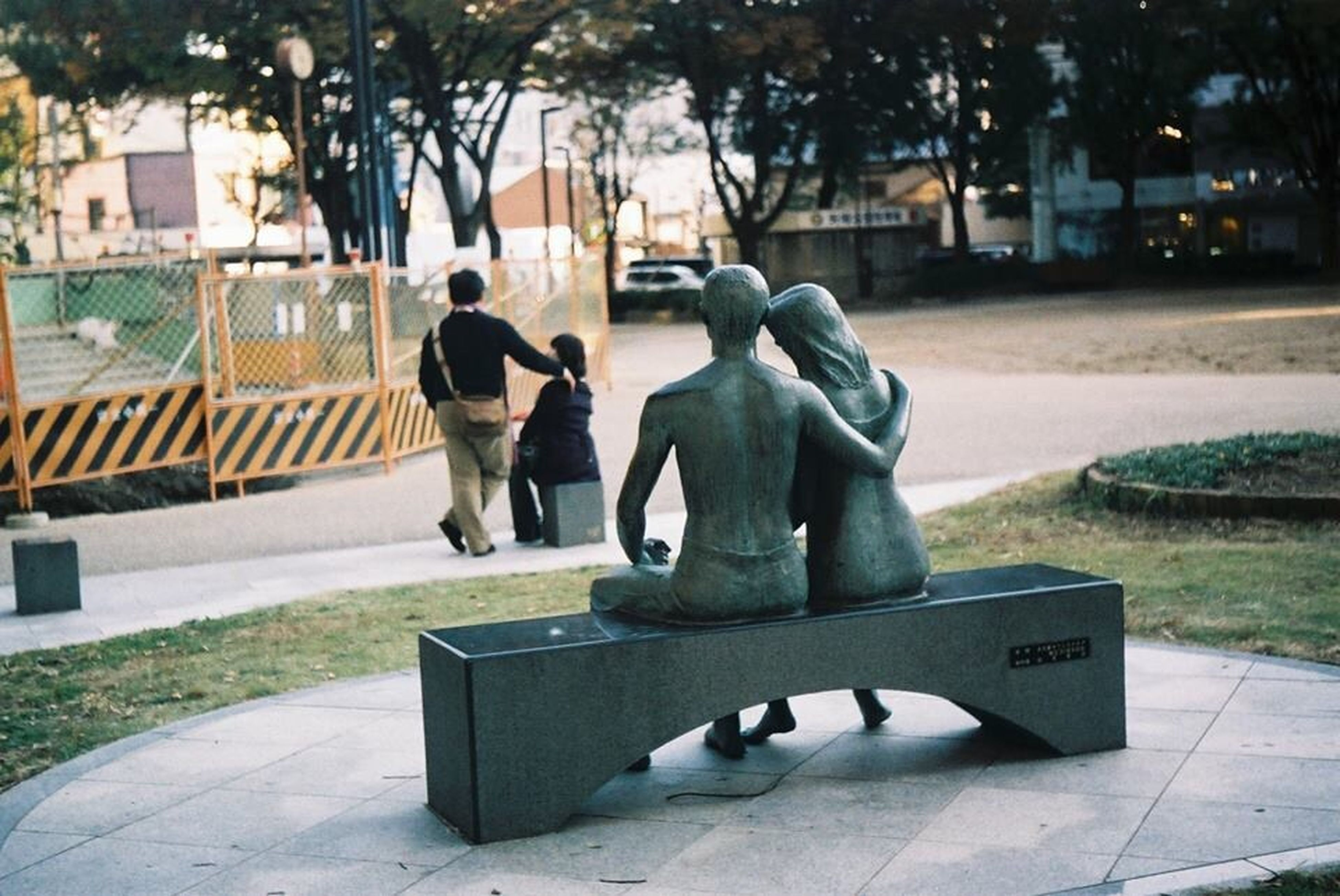 full length, tree, built structure, building exterior, architecture, men, lifestyles, leisure activity, human representation, sitting, park - man made space, rear view, city, sunlight, statue, outdoors, sculpture, day
