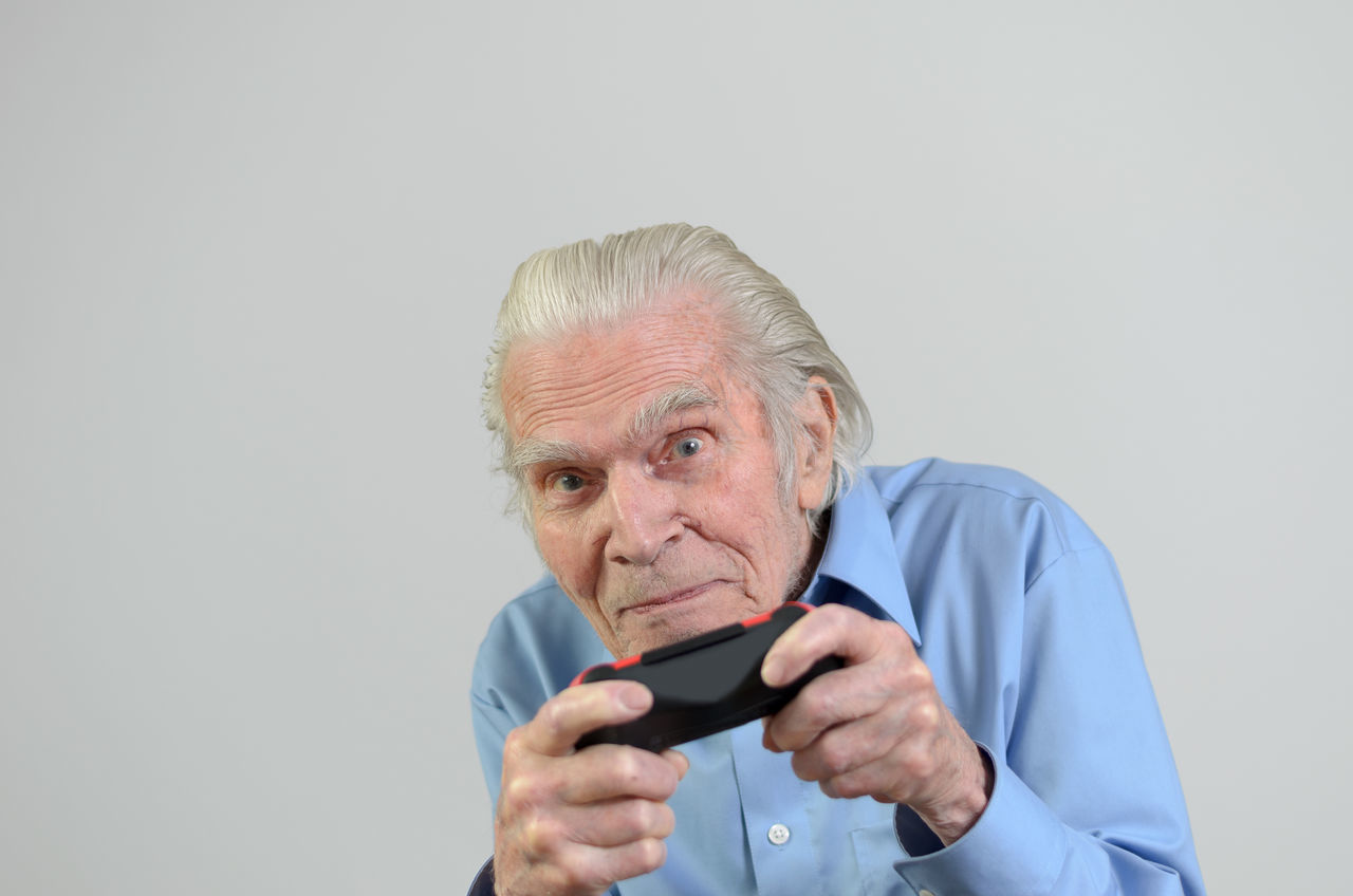 Portrait Of Senior Man Holding Joystick Against Gray Background