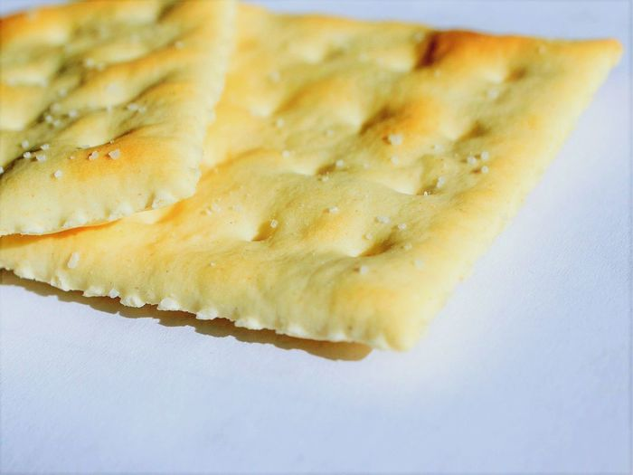 Two crackers Close-up Indoors  Food Saltine Snak Focus On Foreground White Background Day Ready-to-eat Shadow Natural Lighting
