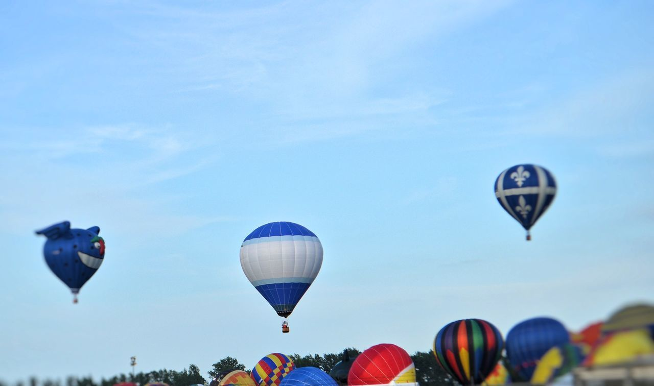 hot air balloon, mid-air, adventure, flying, ballooning festival, transportation, sky, parachute, air vehicle, day, outdoors, extreme sports, multi colored, nature, clear sky, no people
