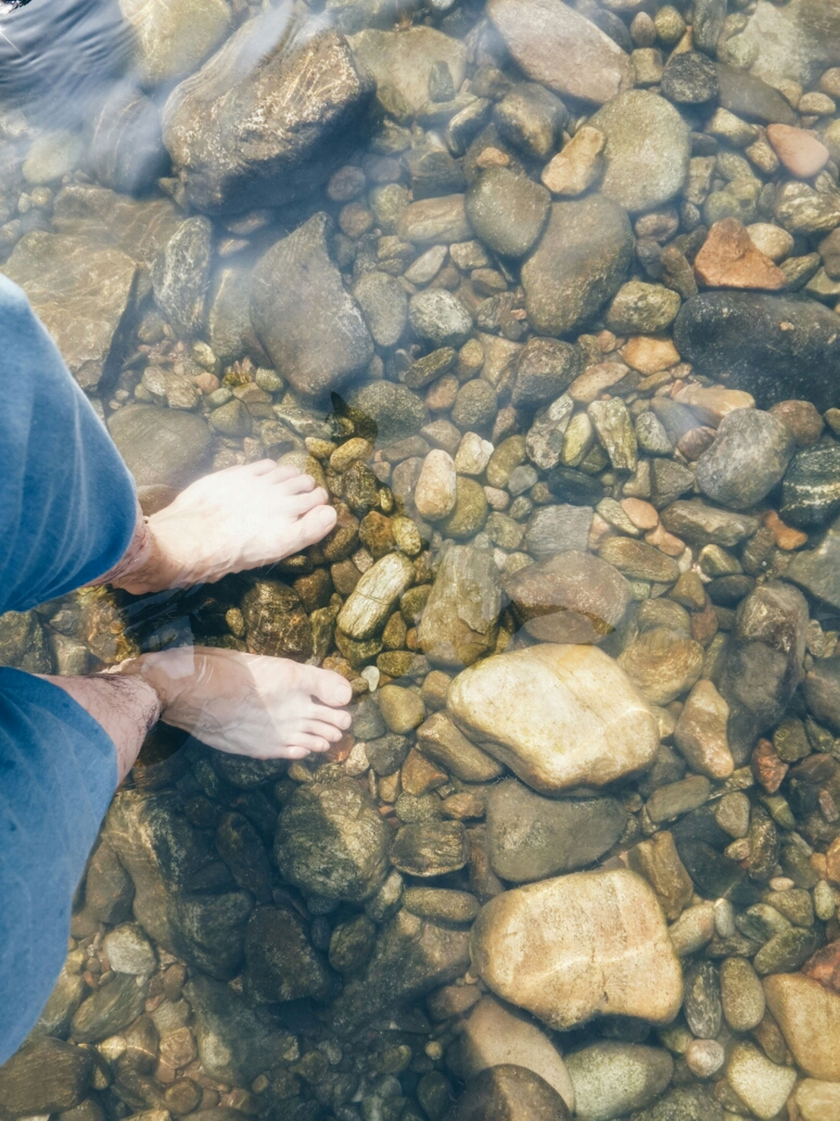 low section, person, water, stone - object, rock - object, high angle view, lifestyles, standing, pebble, leisure activity, personal perspective, nature, unrecognizable person, men, beach, human foot, outdoors