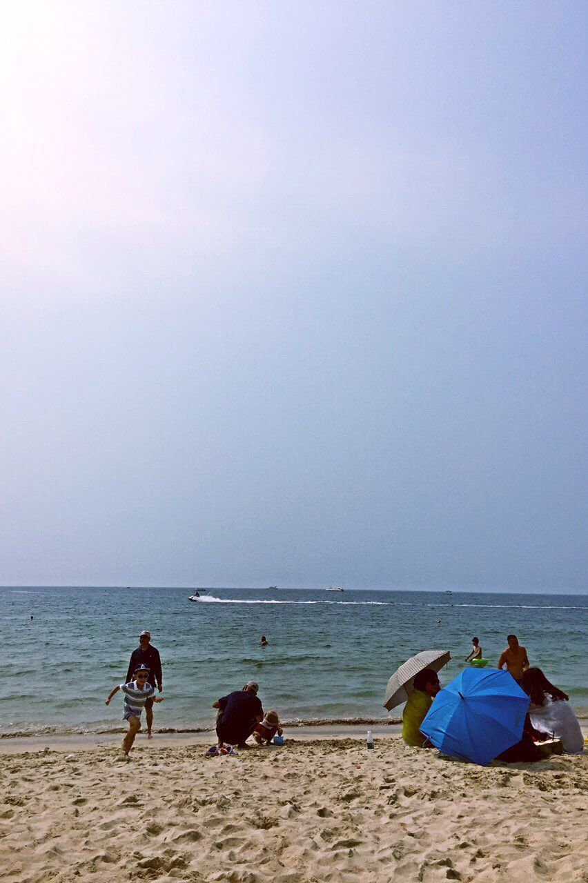 Rear View Of People Relaxing On Beach