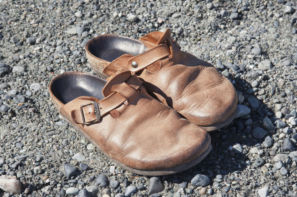 Old Clogs on the Rocks Aged Aging Beauty Of Decay Casual Clothing Clogs Close-up Comfortable Comfortable Shoes Decay Gravel High Angle View Leather No People Old Old-fashioned Pair Pair Of Shoes Pebble Run-down Scratched Shoe Still Life Things That Go Together Torn Wrinkled