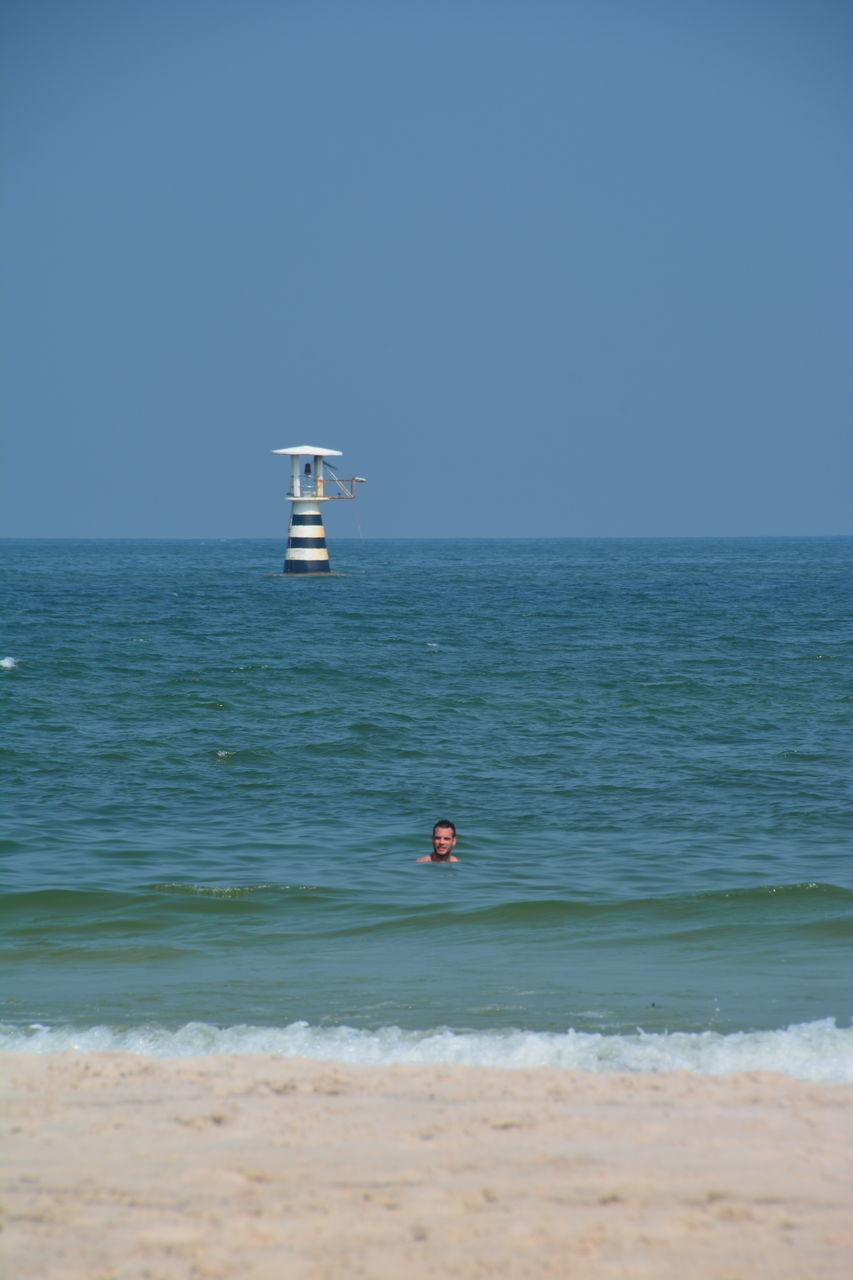 sea, water, horizon over water, beach, nature, scenics, clear sky, tranquility, beauty in nature, tranquil scene, day, outdoors, lighthouse, real people, blue, men, wave, sky, one person, sand, people