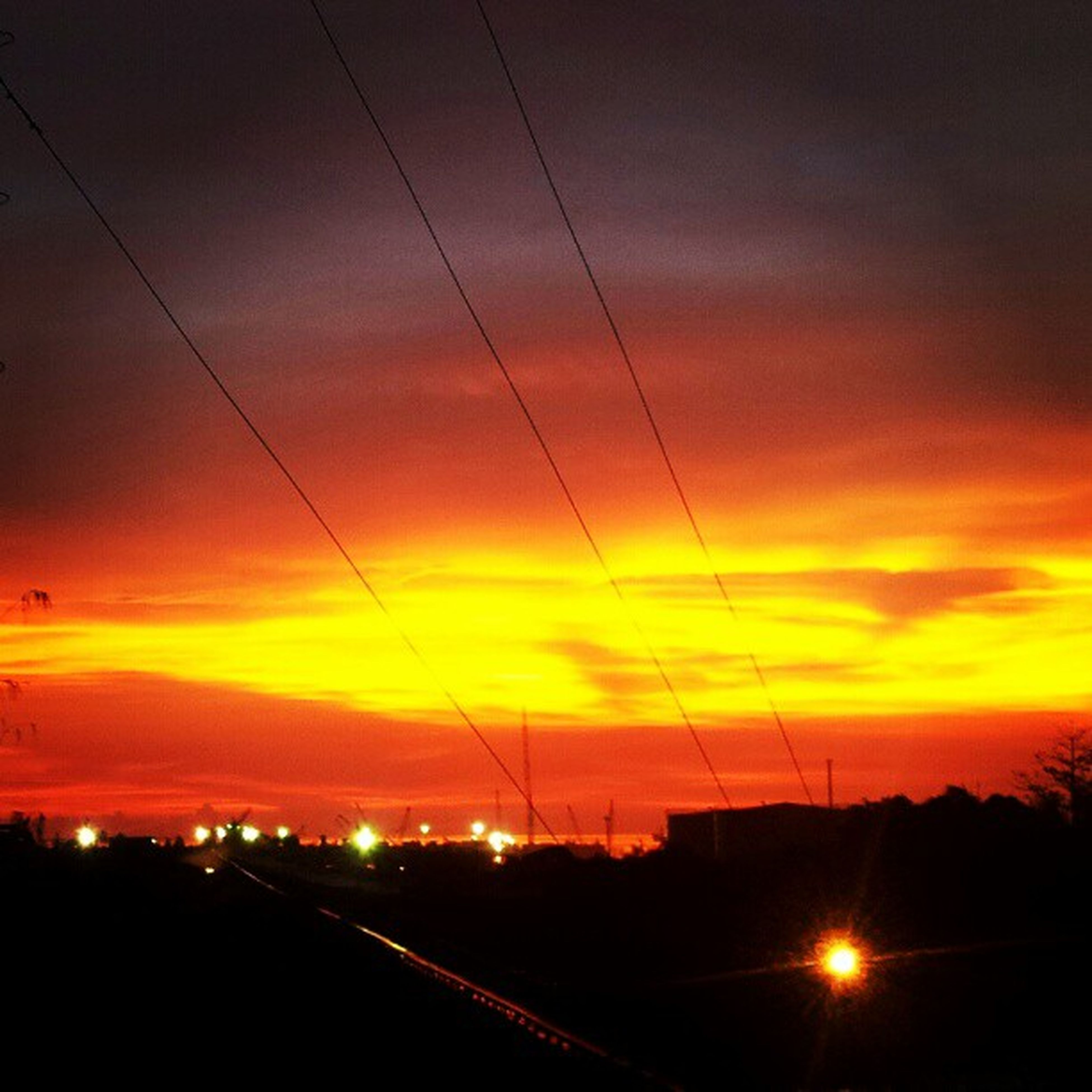 sunset, orange color, sky, power line, cloud - sky, silhouette, electricity pylon, connection, electricity, cable, scenics, beauty in nature, dramatic sky, nature, power supply, tranquility, built structure, idyllic, tranquil scene, landscape