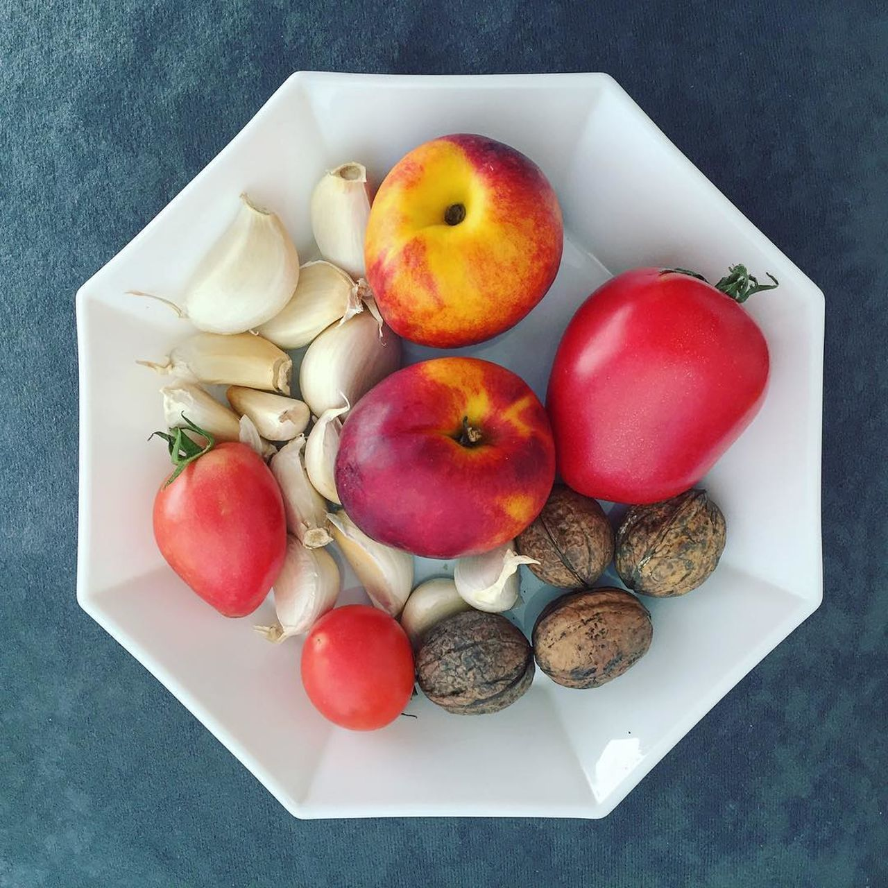 Bowl with raw fruits, vegetables and nuts Close-up Directly Above Food Freshness Fruit Garlic Healthy Eating High Angle View No People Nut Peach Table Tomato