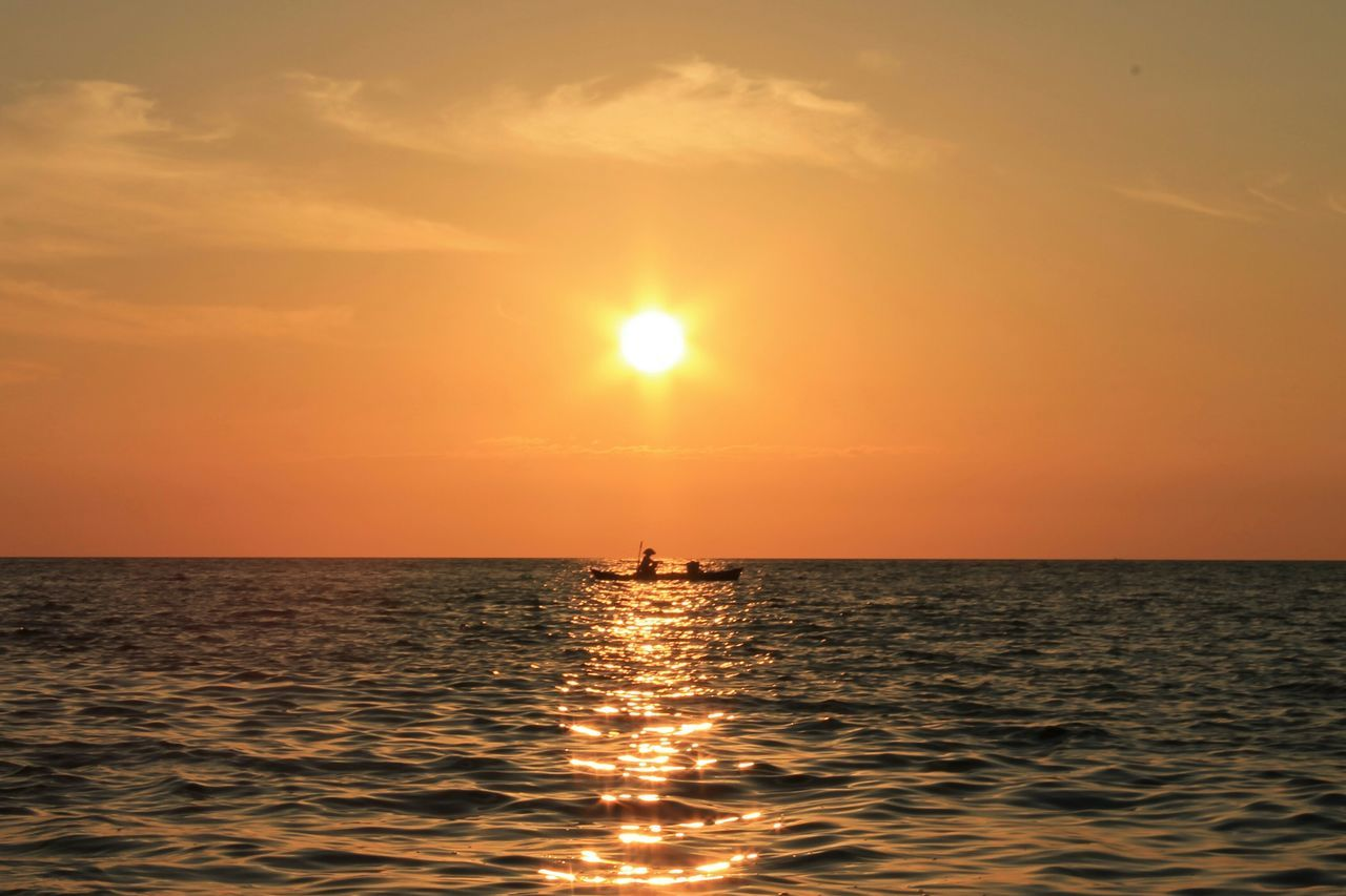 sunset, sea, horizon over water, sun, scenics, water, nature, beauty in nature, orange color, silhouette, reflection, tranquil scene, tranquility, waterfront, sky, idyllic, sunlight, rippled, outdoors, real people, one person, jet boat, people