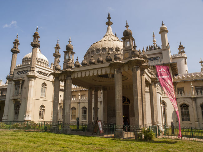 The Royal Pavilion, also known as the Brighton Pavilion, is a former royal residence located in Brighton, England. Beginning in 1787, it was built in three stages as a seaside retreat for George, Prince of Wales, who became the Prince Regent in 1811. It is built in the Indo-Saracenic style prevalent in India for most of the 19th century. The current appearance of the Pavilion, with its domes and minarets, is the work of architect John Nash, who extended the building starting in 1815 Brighton Pavilion Hospital Indian Army John Nash Minarets Prince Of Wales Prince Regent The Royal Pavilion Travel Destinations World War One