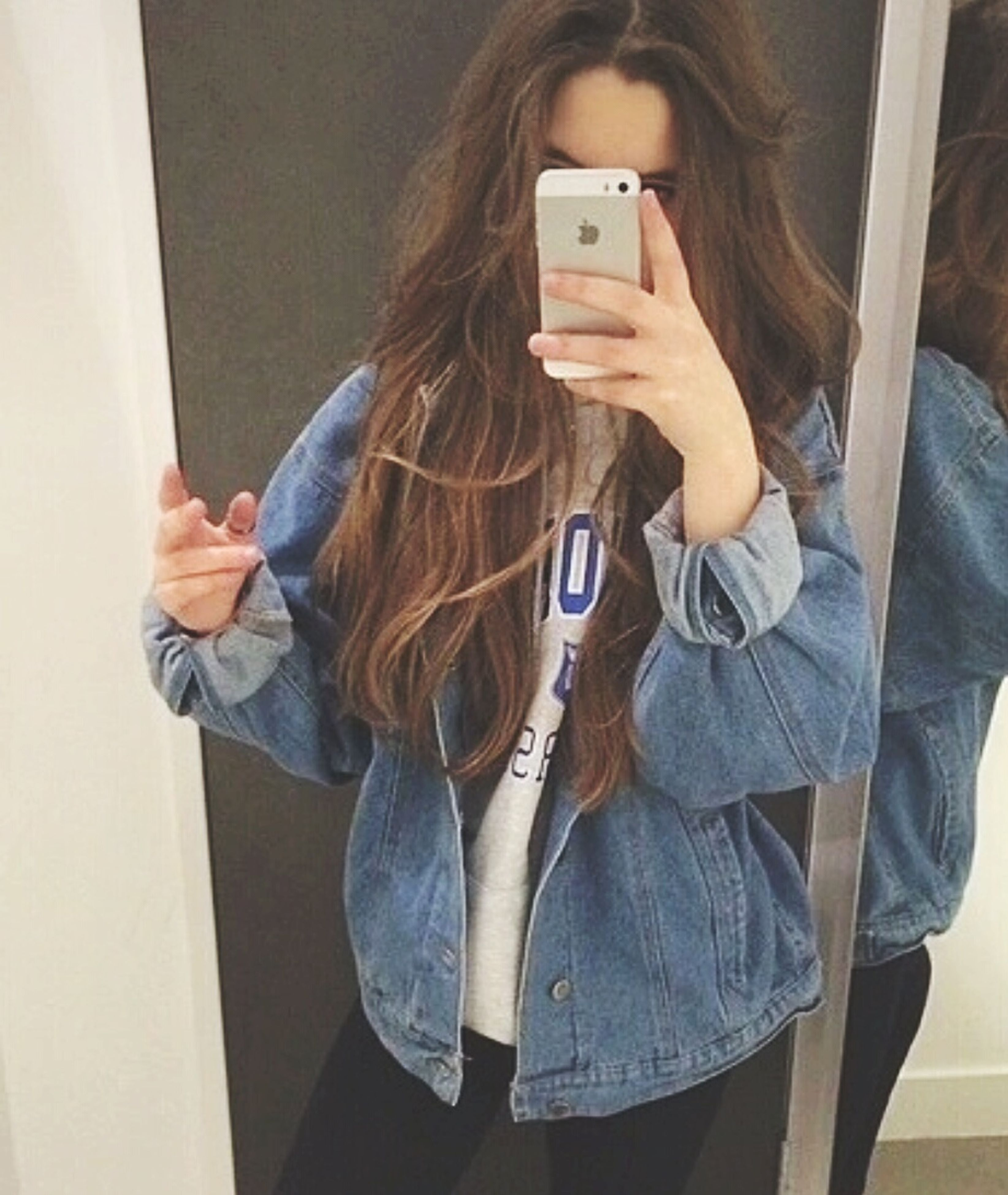 indoors, lifestyles, casual clothing, young adult, leisure activity, person, young women, holding, technology, long hair, standing, front view, three quarter length, wireless technology, wall - building feature, waist up, smart phone, home interior