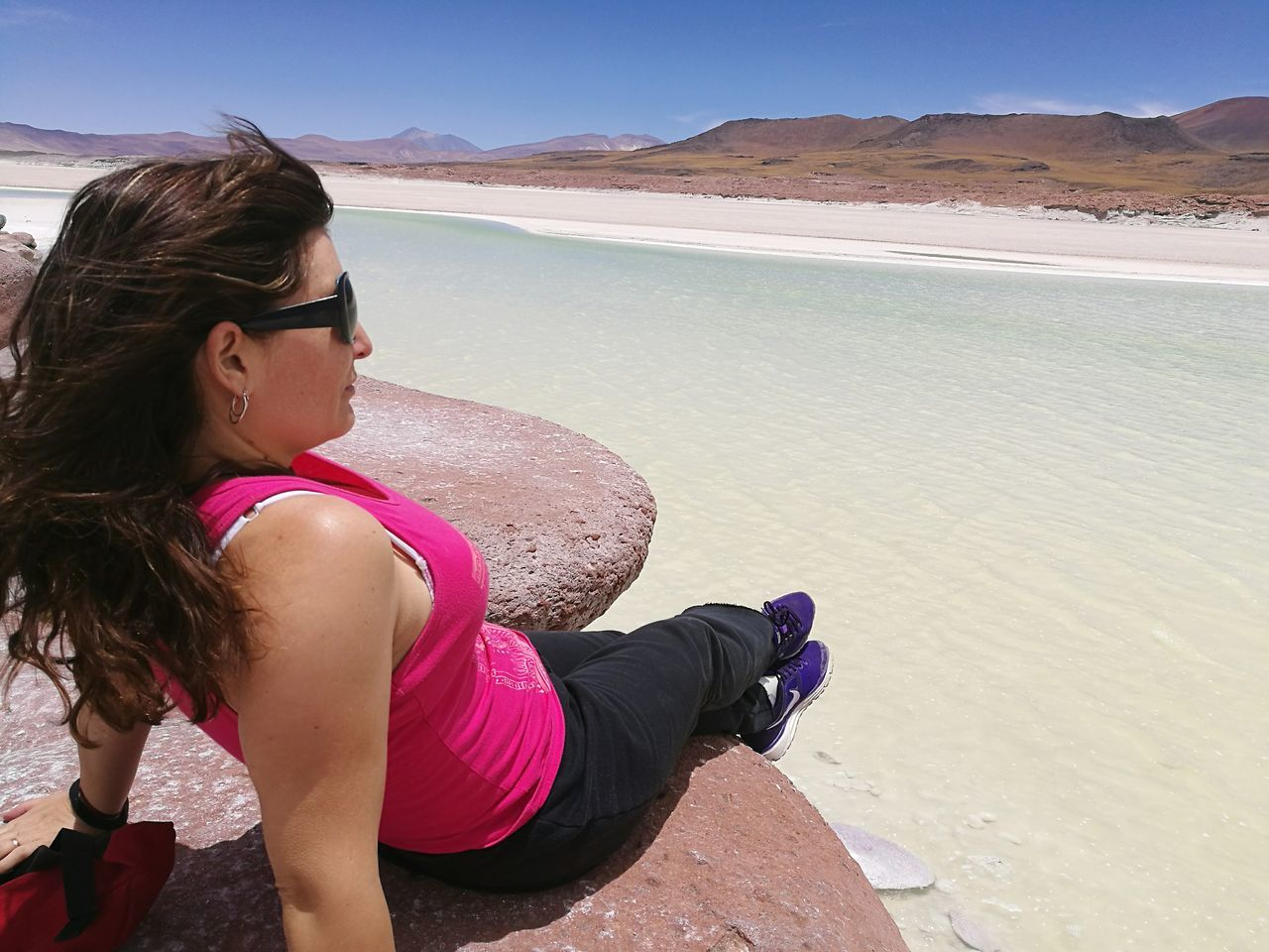 Full Length Of Woman Relaxing On Rock At Lake