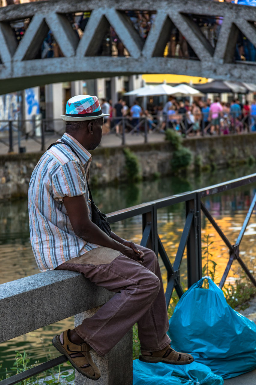 real people, full length, one person, casual clothing, lifestyles, sitting, focus on foreground, leisure activity, outdoors, day, architecture, men, headwear, young adult, people