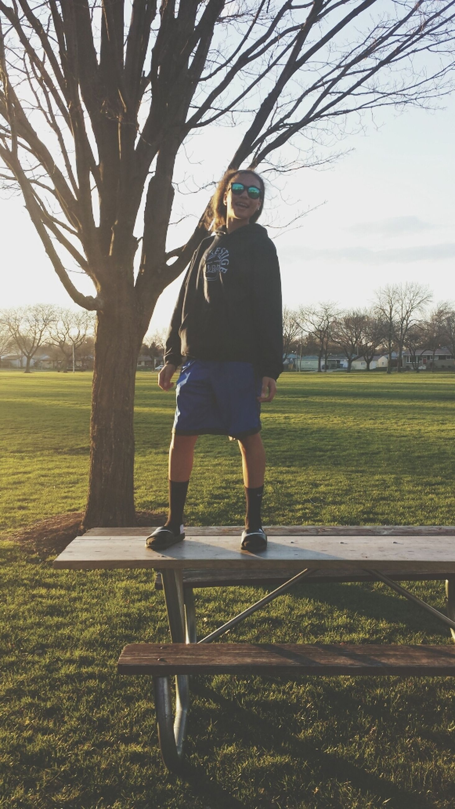 tree, full length, lifestyles, leisure activity, grass, casual clothing, park - man made space, childhood, field, rear view, sky, sunlight, swing, men, day, outdoors, boys, park