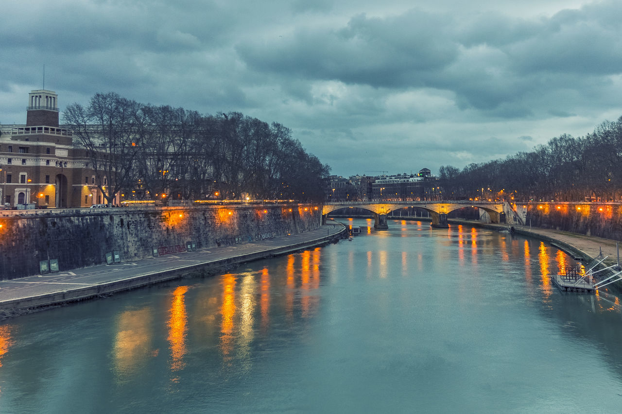 architecture, built structure, water, bridge - man made structure, cloud - sky, connection, sky, building exterior, weather, reflection, outdoors, waterfront, tree, river, no people, city, travel destinations, illuminated, day, nature, chain bridge