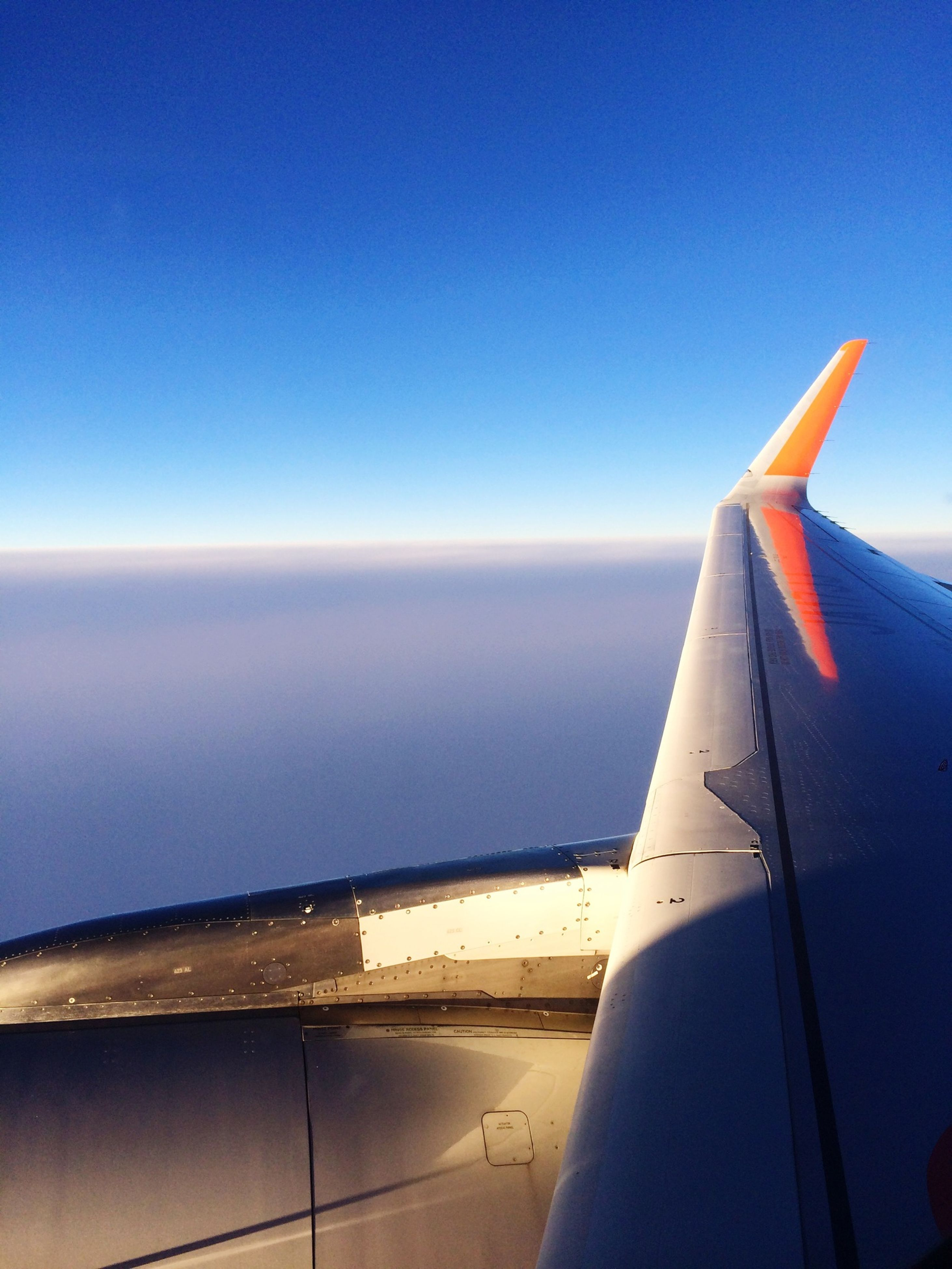 airplane, aircraft wing, sea, air vehicle, transportation, part of, blue, cropped, horizon over water, flying, mode of transport, sky, scenics, travel, journey, beauty in nature, clear sky, aerial view, nature, copy space