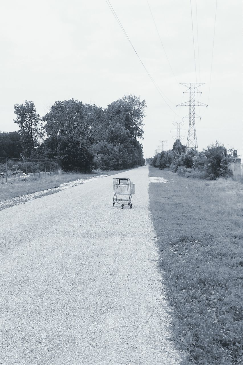 Shopping Cart On Road By Field Against Sky