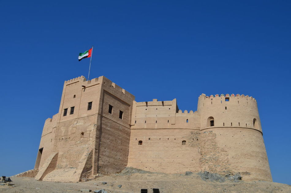 Architecture Blue Sky Building Exterior Clear Sky Day Flag Fort Fortress Fujairah Historical Building History No People Outdoors Sky Travel Travel Destinations UAE United Arab Emirates