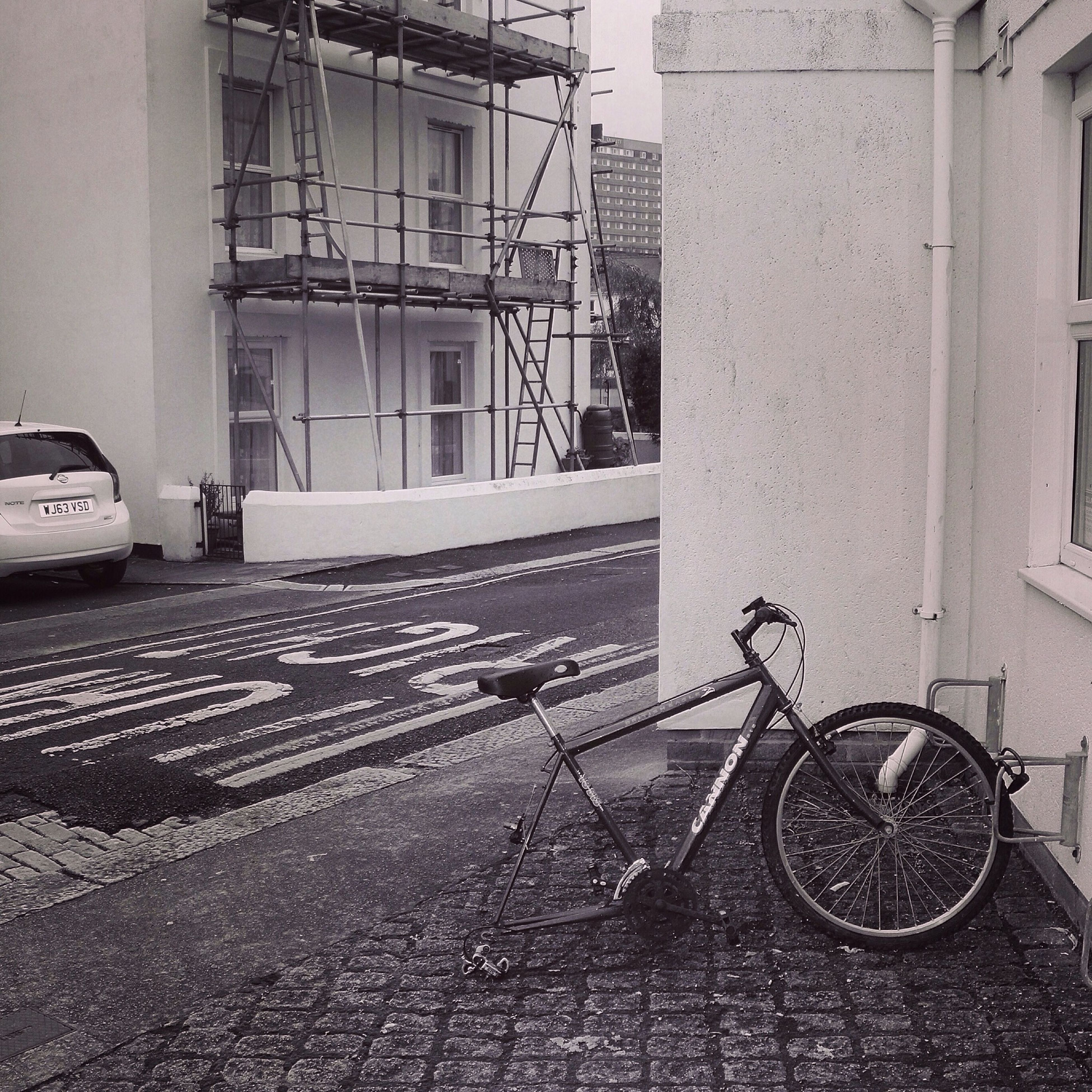 building exterior, architecture, built structure, transportation, bicycle, mode of transport, land vehicle, street, parked, stationary, building, parking, city, cobblestone, day, sidewalk, window, house, residential structure, outdoors