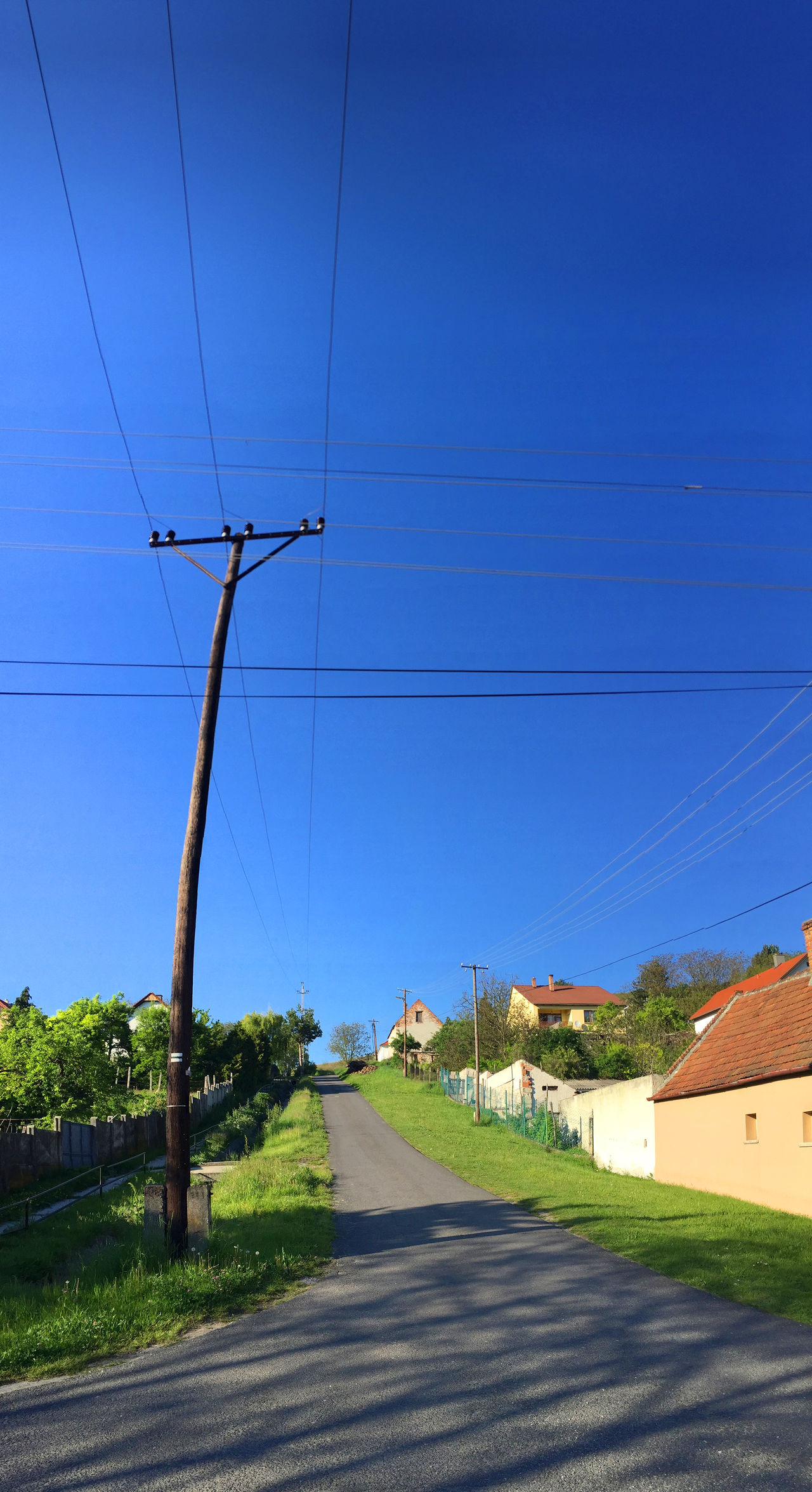Blue Built Structure Cable Clear Sky Day Diminishing Perspective Electricity  Electricity Pylon Empty Long No People Outdoors Power Cable Power Line  Power Supply Road Sky Steep Streetphotography The Way Forward Vanishing Point Village