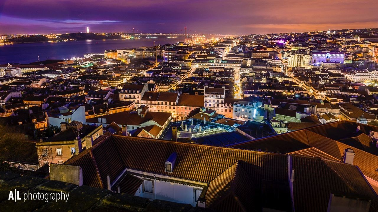 architecture, building exterior, cityscape, illuminated, sky, built structure, night, city, outdoors, high angle view, sunset, cloud - sky, no people, travel destinations, sea, scenics, skyscraper, urban skyline, beauty in nature, nature
