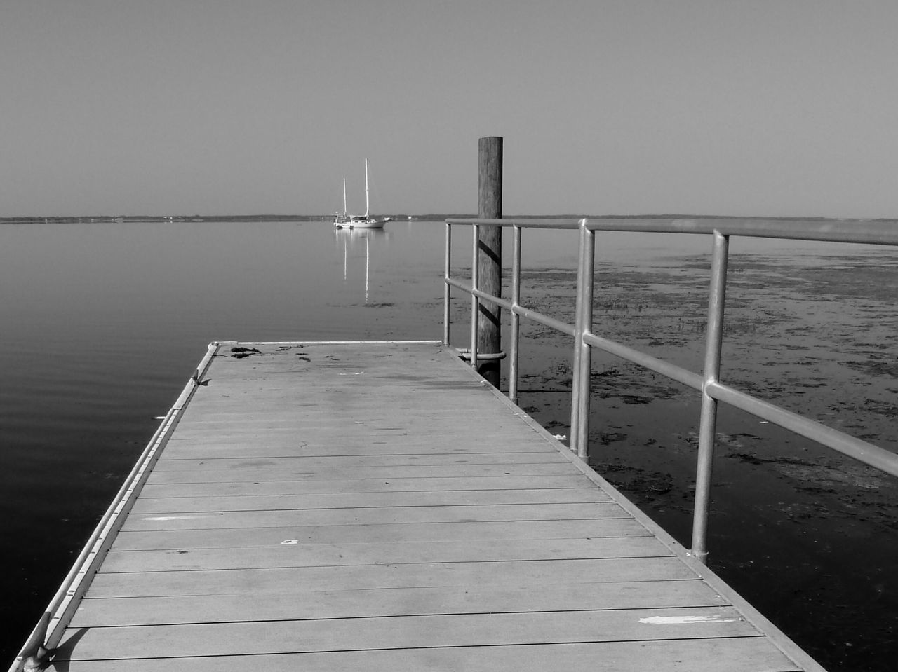 Sailboat Nautical Vessel Boat Dock Water Tree Line Riverside Reflection From A Distance Black And White Photography
