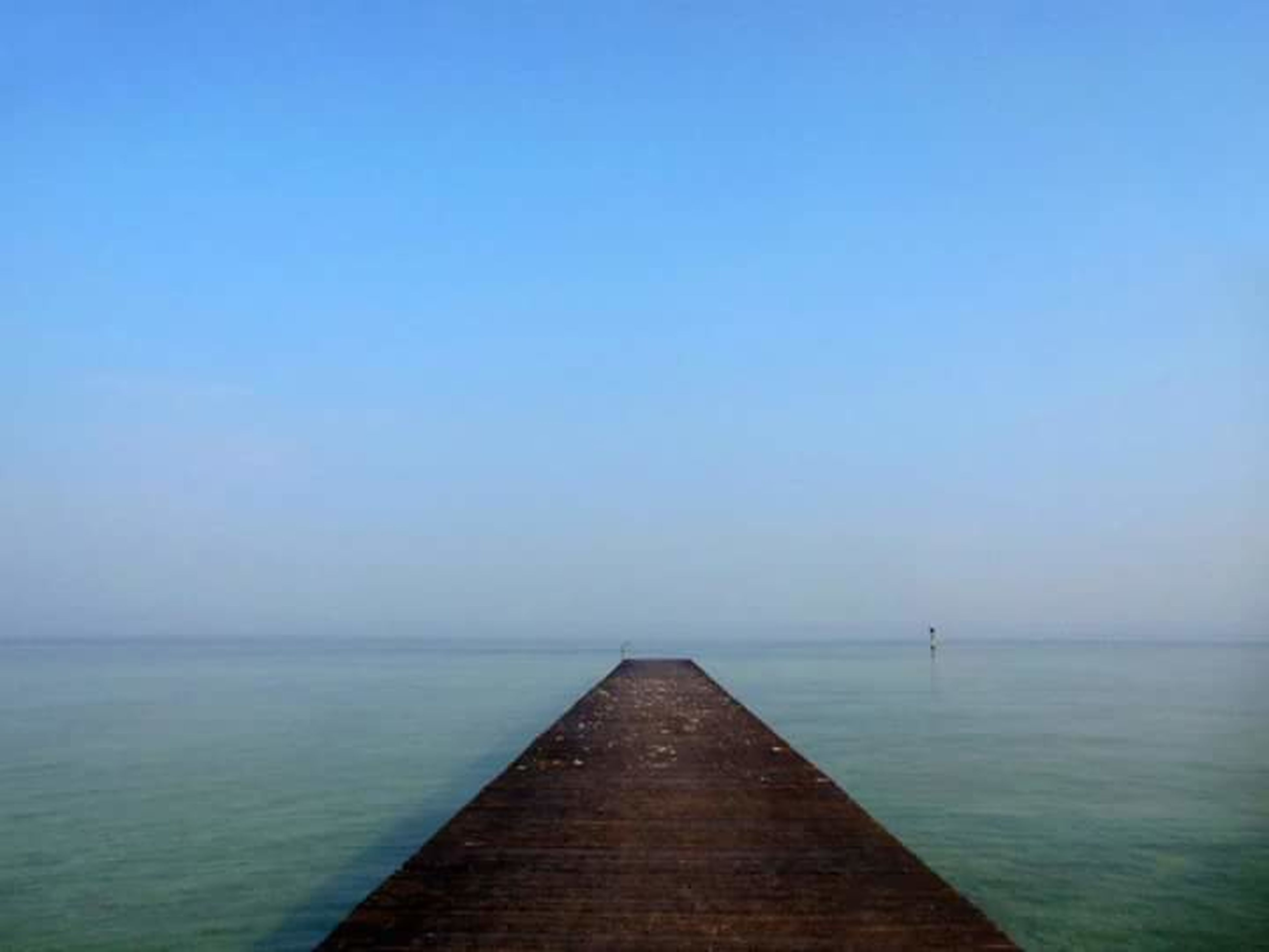 sea, horizon over water, copy space, water, clear sky, tranquil scene, tranquility, scenics, beauty in nature, blue, nature, pier, idyllic, waterfront, seascape, calm, sky, the way forward, ocean, jetty