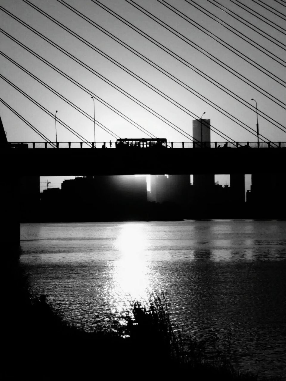 connection, bridge - man made structure, cable, built structure, architecture, sky, water, river, transportation, no people, bridge, electricity pylon, outdoors, day, electricity, silhouette, building exterior, suspension bridge, travel destinations, nature, clear sky, city