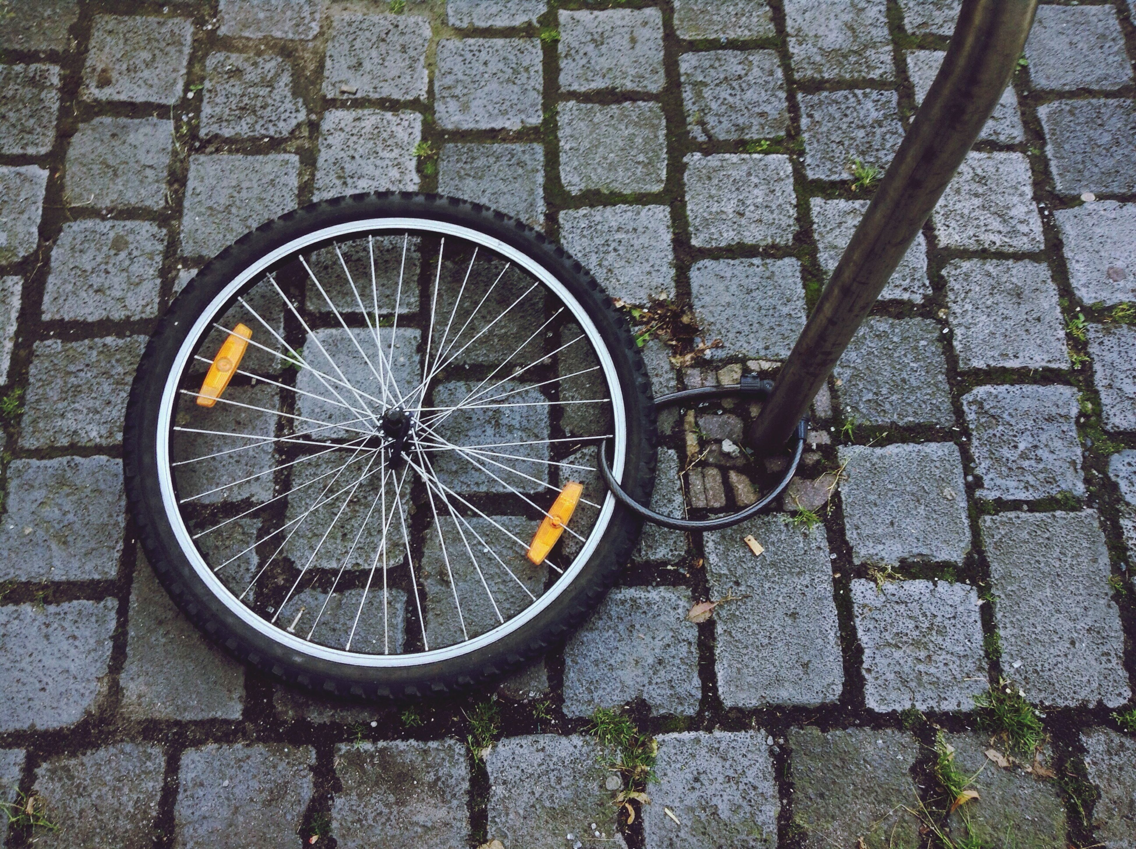 High Angle View Of Bicycle Wheel On Paving Footpath