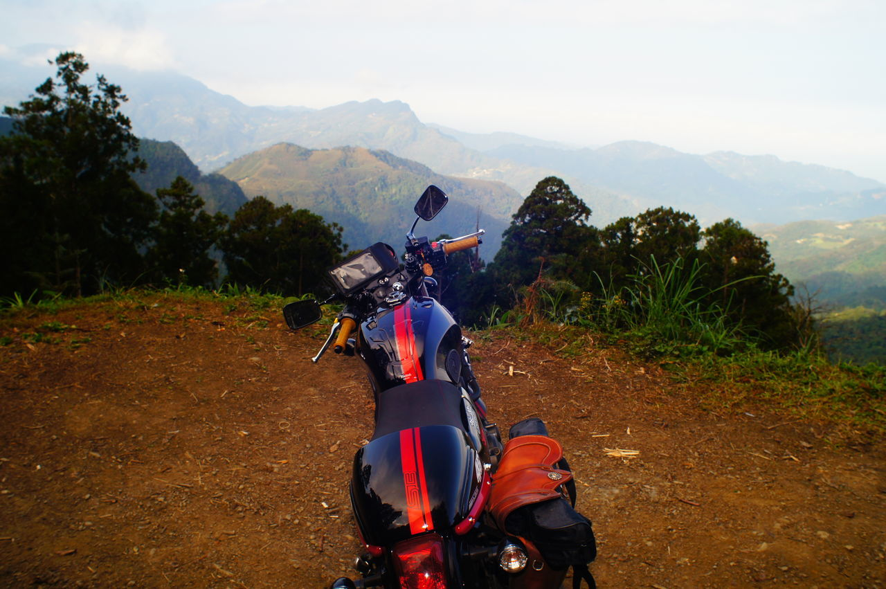 mountain, motorcycle, field, transportation, sky, real people, landscape, outdoors, day, nature, tree, helmet, riding, adventure, men, land vehicle, mountain range, sports helmet, beauty in nature, scenics, one person, motocross, mammal, people