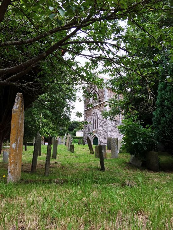 Local Cemetery Graveyard peaceful setting in the Cornish Village Tombstone and Gravestone amongst the Green Grass Spirituality is at the centre, Church sits surrounded by Crosses & Headstones EyeEm Selects Colour Of Life fades to Memories Inscribed in Stone EyeEm Gallery My Point Of View Shapes And Forms Textures And Surfaces Beautiful Cornwall Church Architecture Trees covering the Pathway to the Entrance , Moss in abundance
