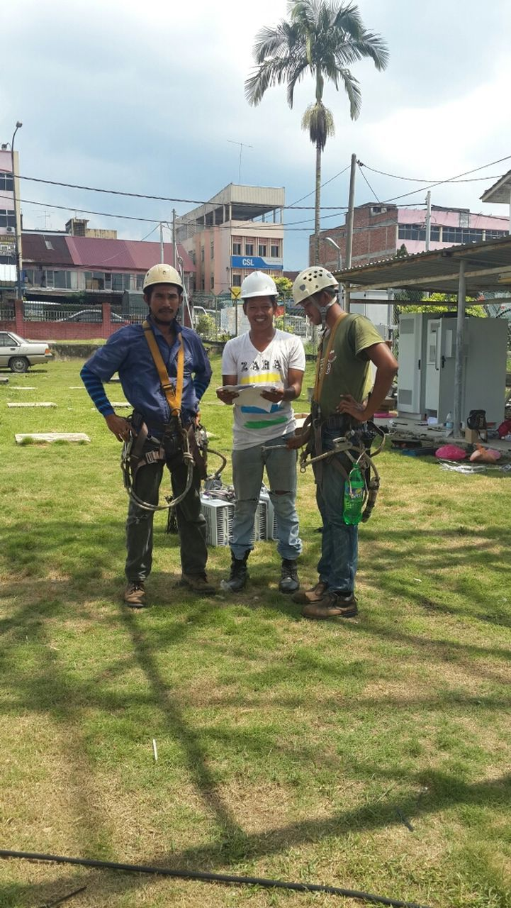 men, protective workwear, grass, day, protection, safety, real people, occupation, full length, standing, field, tree, helmet, teamwork, outdoors, headwear, sky, building exterior, architecture, adult, people