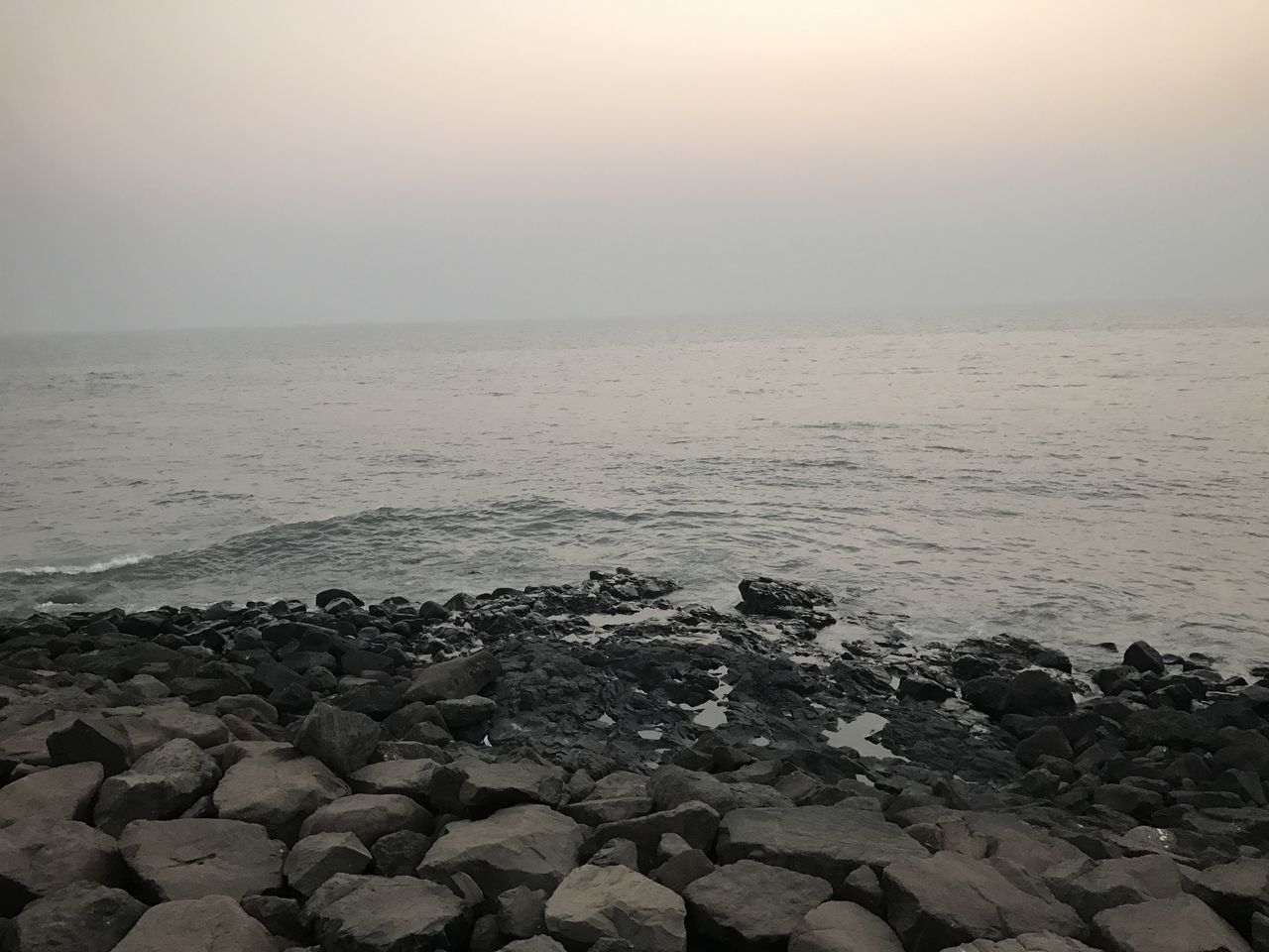 sea, beauty in nature, nature, pebble, pebble beach, water, tranquil scene, shore, tranquility, horizon over water, beach, scenics, no people, outdoors, rock - object, sky, sunset, clear sky, day