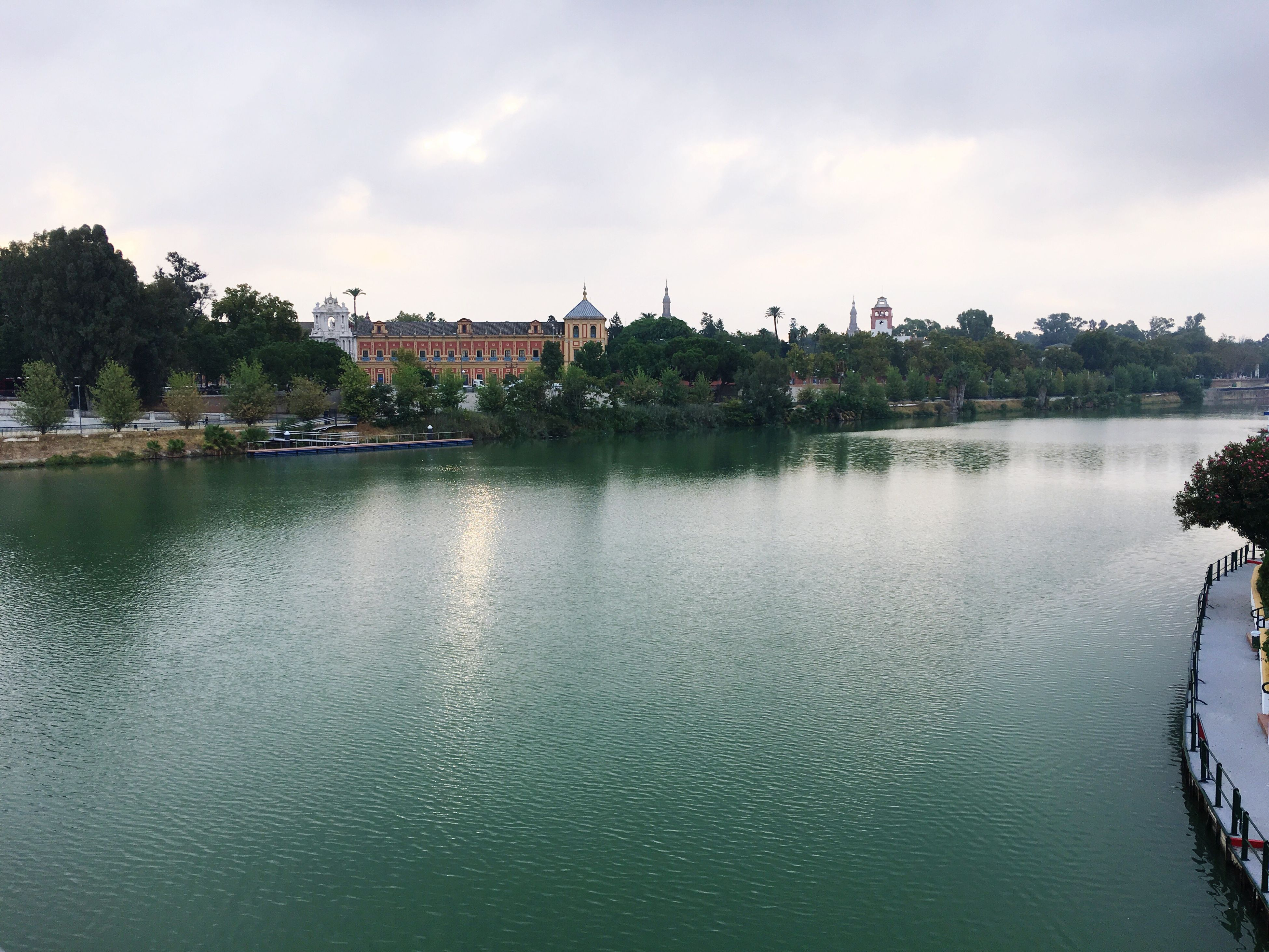 water, architecture, built structure, building exterior, sky, tree, waterfront, tranquility, tranquil scene, scenics, river, travel destinations, cloud, cloud - sky, day, nature, outdoors, town, no people, beauty in nature, tourism, city life, riverbank