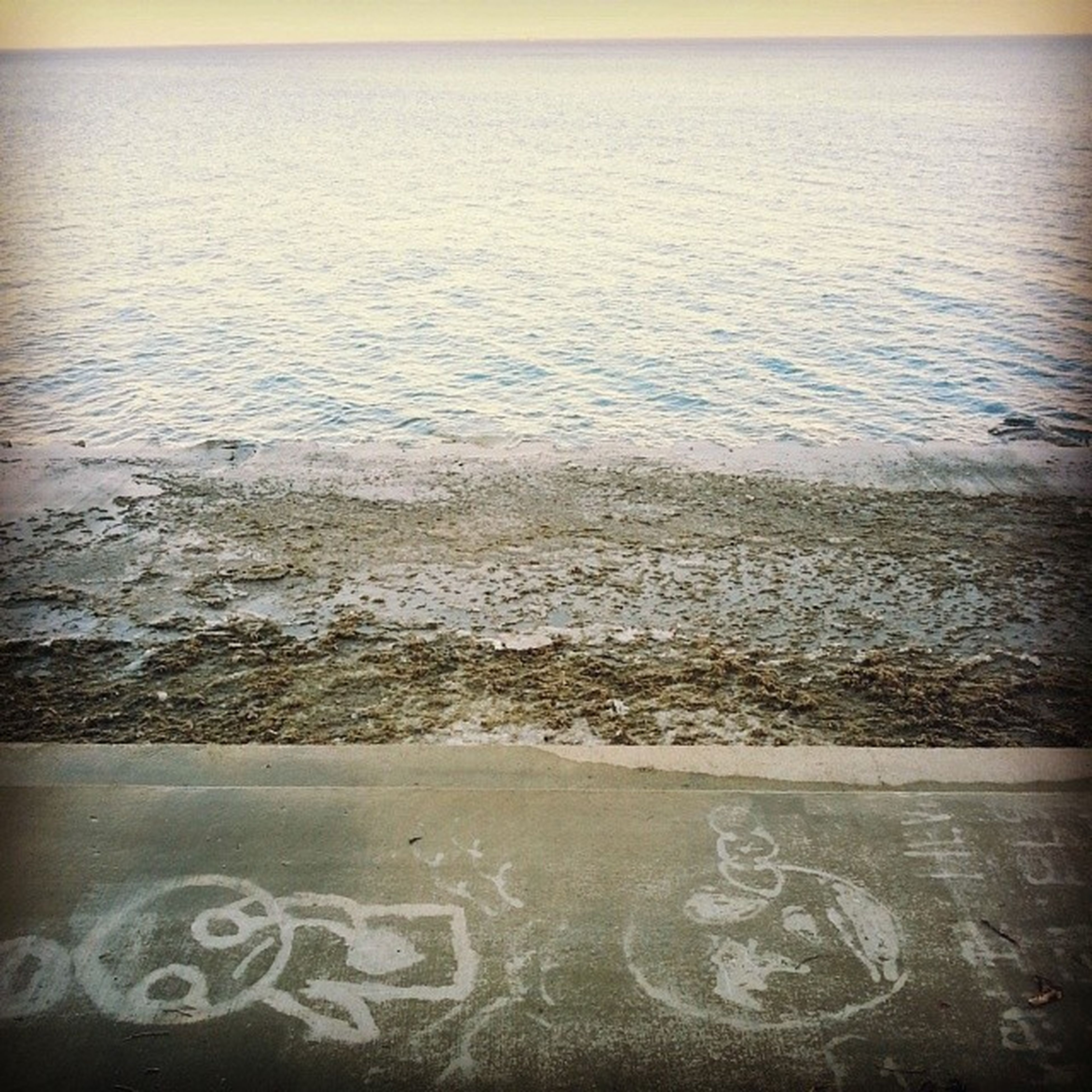 water, sea, horizon over water, beach, shore, tranquil scene, text, tranquility, scenics, nature, beauty in nature, western script, sand, wave, rippled, idyllic, sky, outdoors, no people, communication