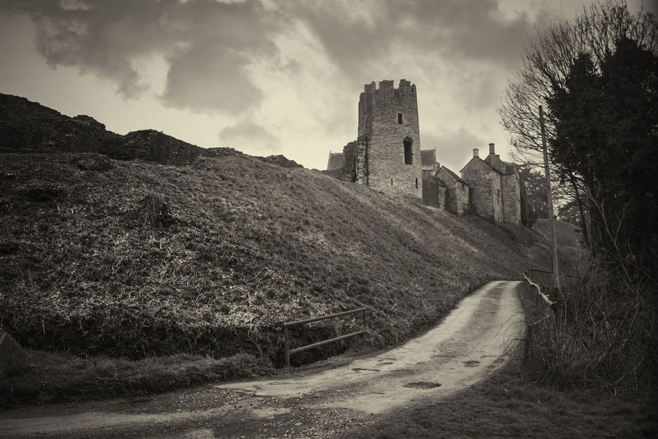 A stronghold upon the brow of the hill, maybe it offers lodgings or a mug of ale. Maybe in its heyday it did but unfortunately not anymore. It stands wasting away through time only as a thing of beauty now. Castles are enchanting, they have a particular type of mystery to them. Neither of us can fully imagine how they operated or looked in their day but I can imagine them being very domineering yet delightfully grand. Architecture Battlements Building Exterior Built Structure Castle Cloud - Sky Day History History] Low Angle View Mountain Nature No People Outdoors Sepia Sky Tones Travel Destinations Tree