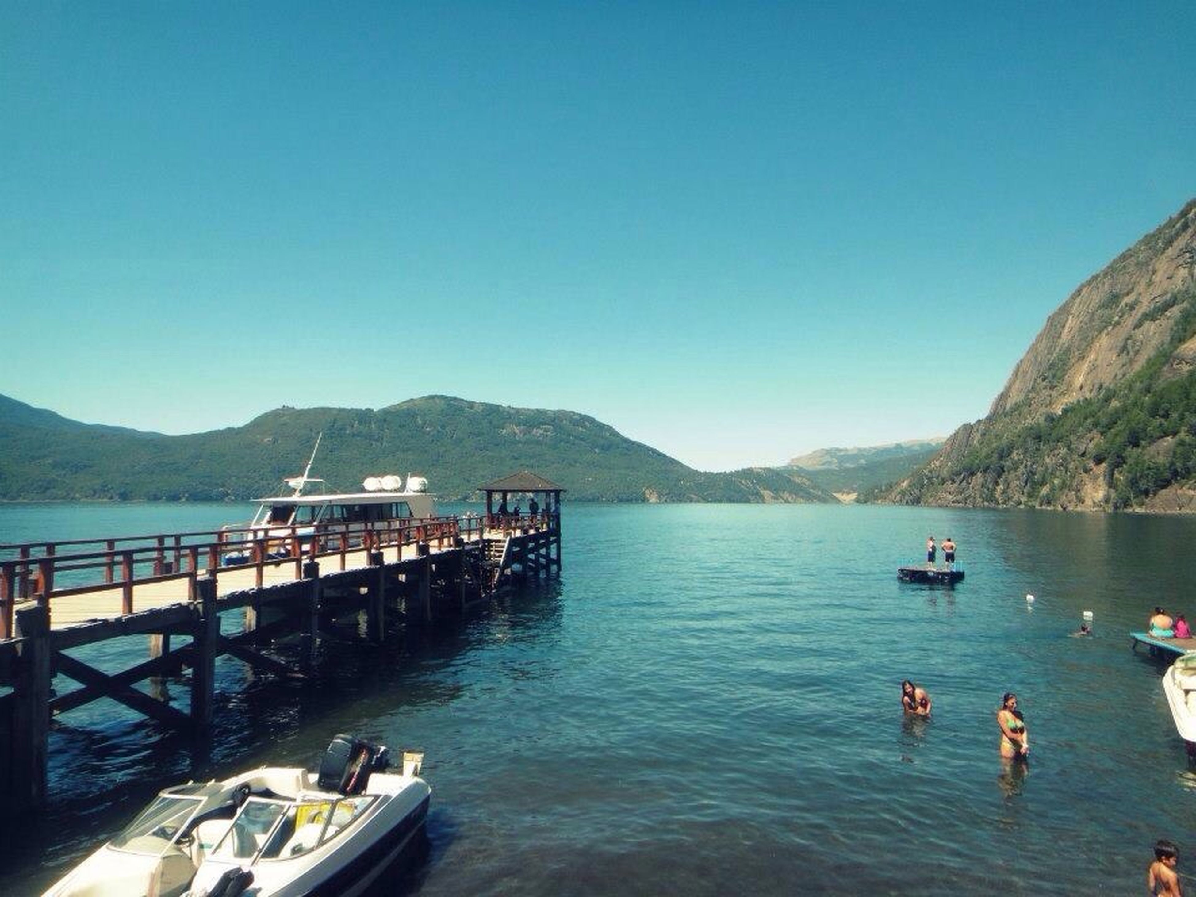 mountain, water, clear sky, copy space, mountain range, blue, nautical vessel, transportation, tranquility, tranquil scene, scenics, pier, beauty in nature, lake, nature, sea, boat, railing, mode of transport, day