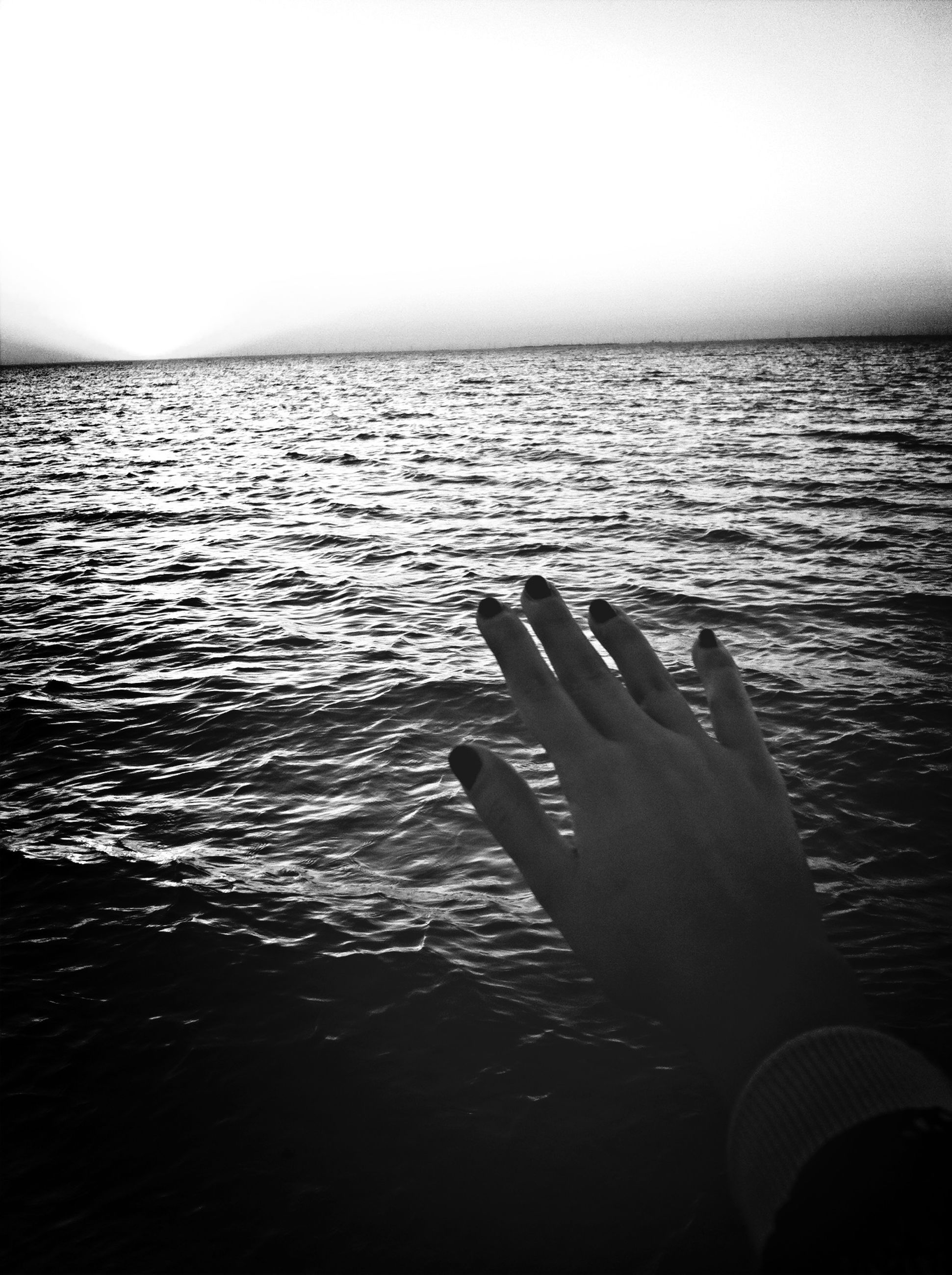water, sea, part of, copy space, clear sky, tranquility, horizon over water, rippled, tranquil scene, cropped, personal perspective, scenics, nature, beauty in nature, person, unrecognizable person