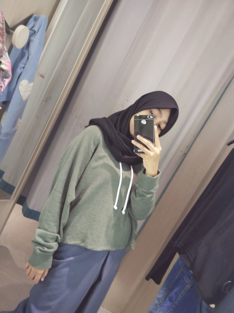 real people, three quarter length, one person, hood - clothing, hooded shirt, leisure activity, casual clothing, lifestyles, young adult, day, technology, standing, outdoors, young women