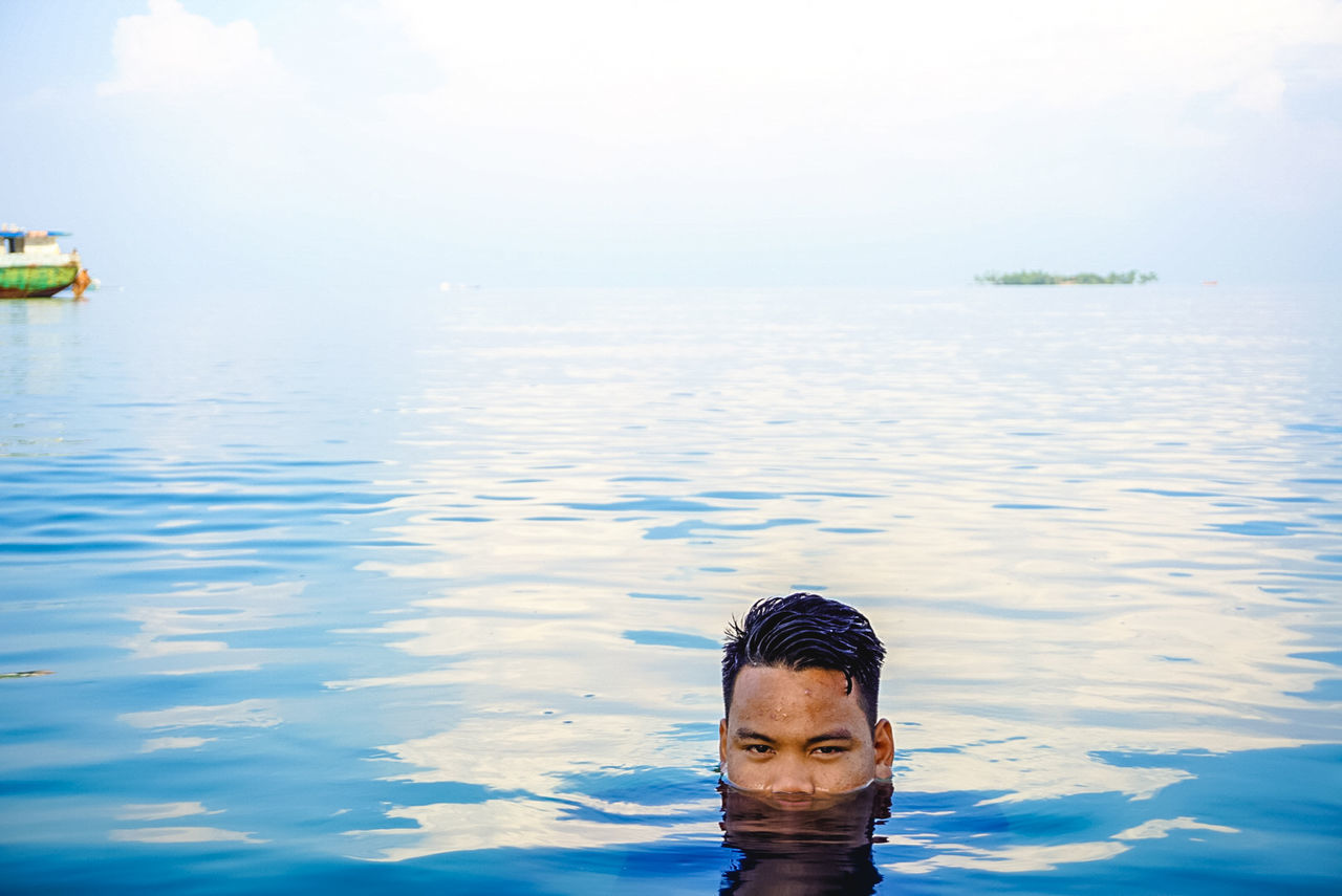 Portrait Of Young Man Swimming In Sea Against Sky