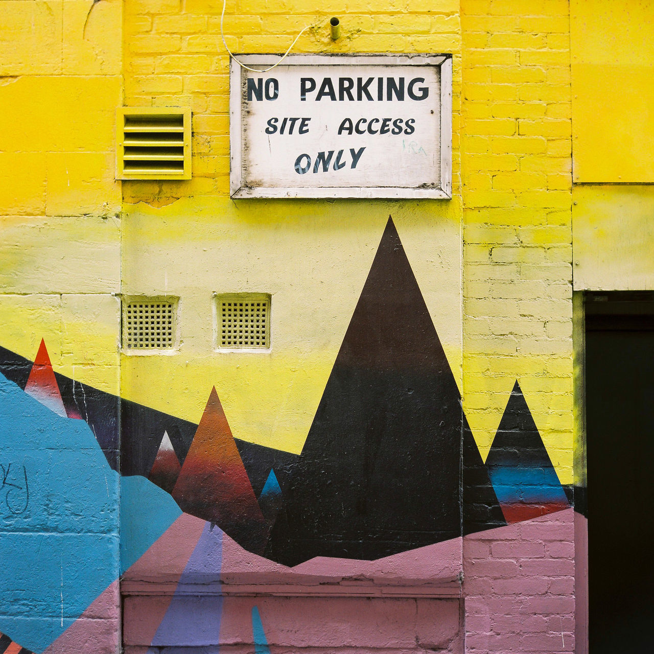 Colourful abstract artwork points toward a no parking sign in a small alley in Glasgow's city centre. Abstract Angles Art Brick Building Exterior Color Colorful Day Film Funky Glasgow  Graffiti Mural Neighborhood Map No Parking No Parking Sign Outdoors Scotland Sign Square Text Triangle Wall - Building Feature Western Script Yellow
