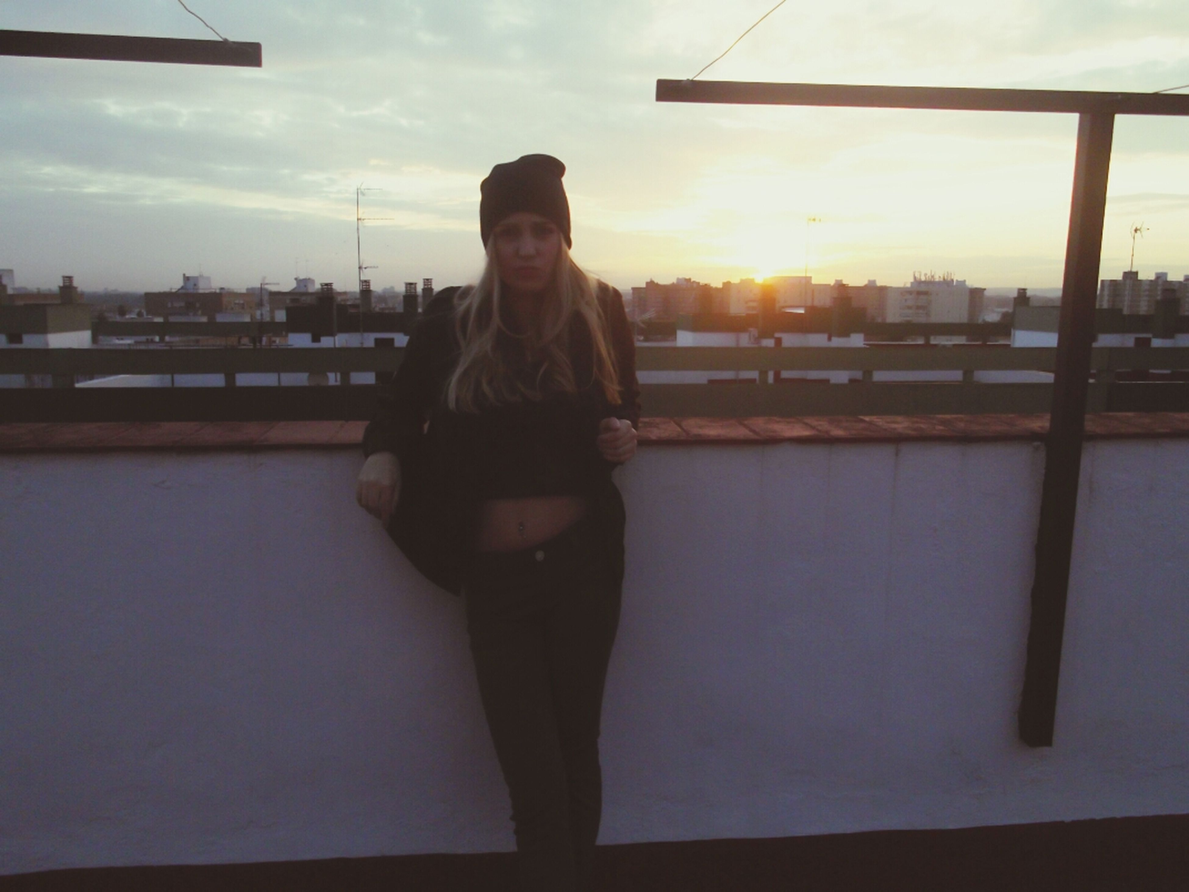 standing, lifestyles, young adult, building exterior, built structure, architecture, casual clothing, leisure activity, full length, three quarter length, sky, sunset, person, young women, railing, front view, city, sunlight