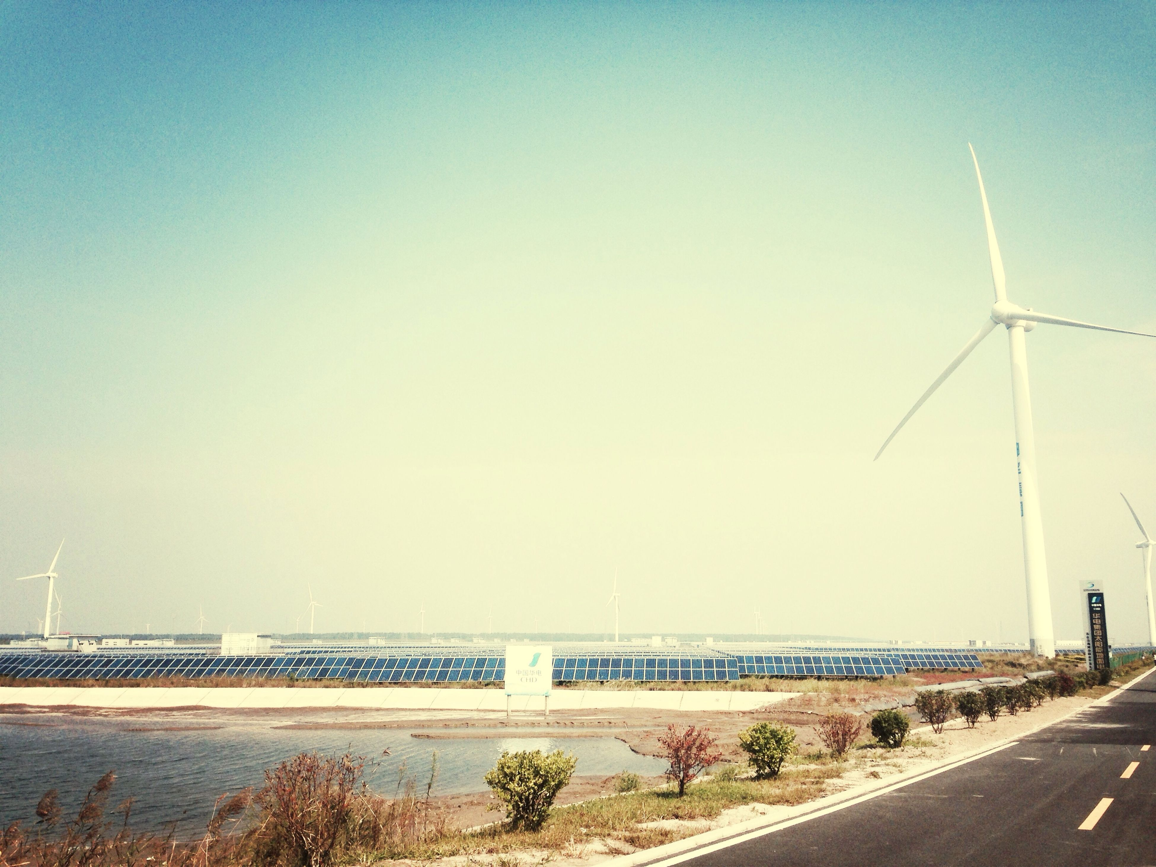 clear sky, copy space, road, wind turbine, fuel and power generation, transportation, alternative energy, wind power, environmental conservation, renewable energy, landscape, windmill, tranquility, the way forward, field, electricity pylon, tranquil scene, day, nature, outdoors