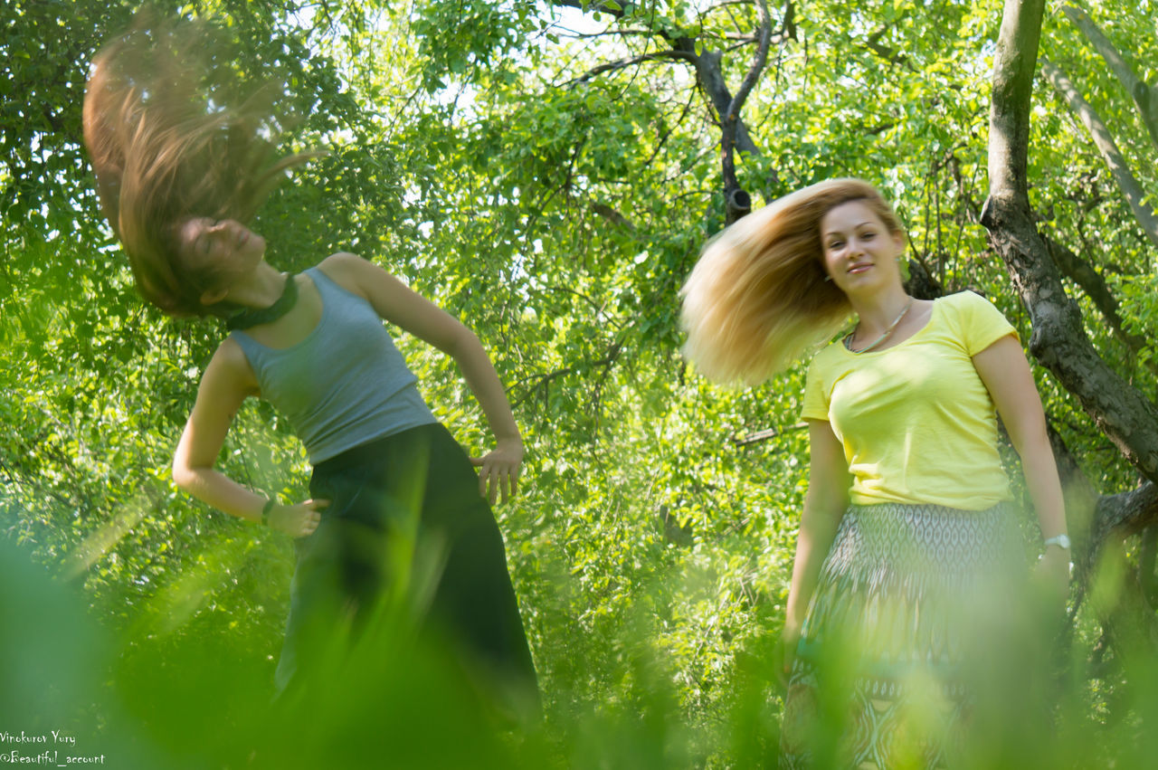 tree, green color, nature, two people, day, real people, casual clothing, togetherness, leisure activity, outdoors, growth, low angle view, grass, childhood, branch, young women, blond hair, beauty in nature, young adult