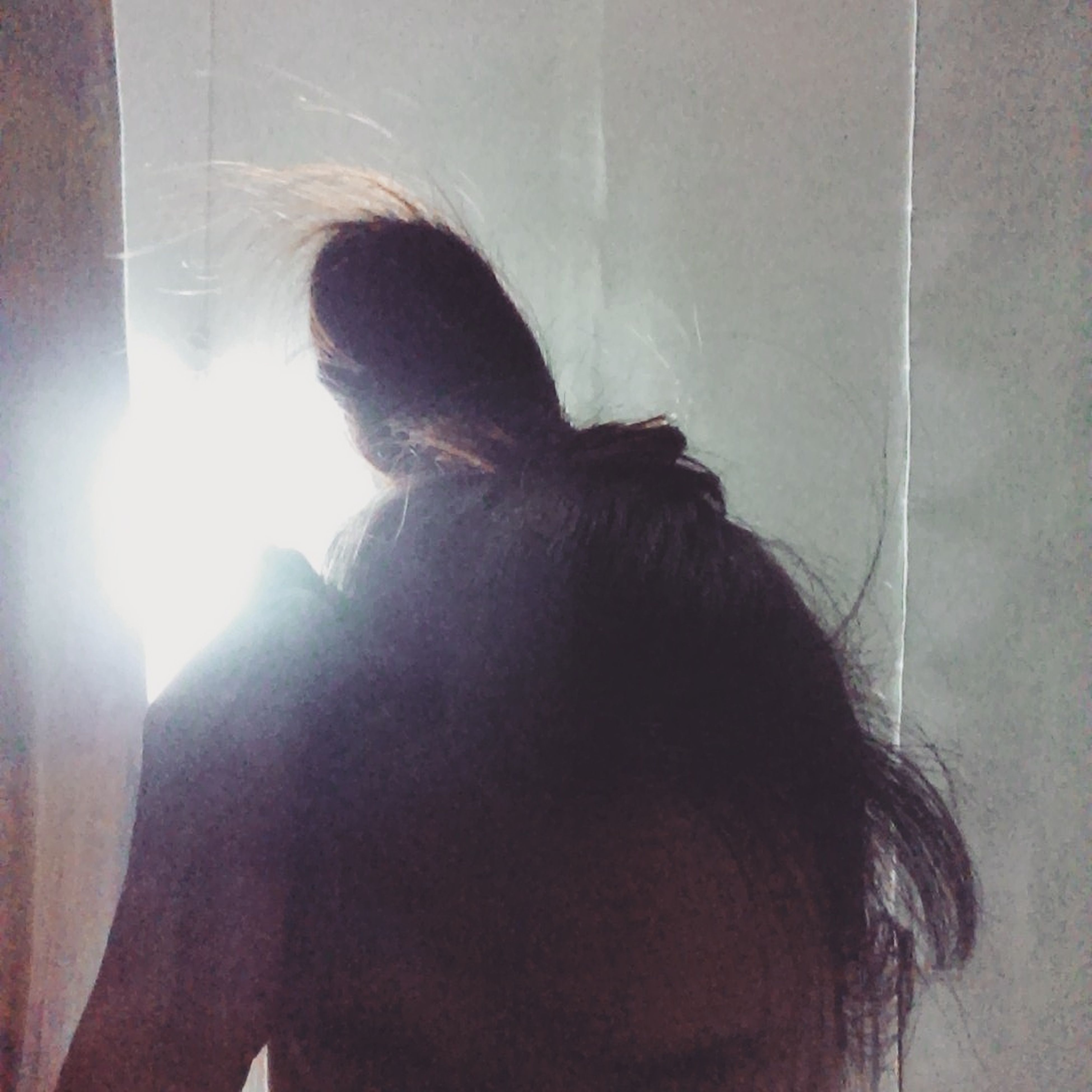 indoors, young adult, lifestyles, headshot, home interior, young women, leisure activity, wall - building feature, long hair, person, sunlight, domestic room, contemplation, front view, curtain, side view, window