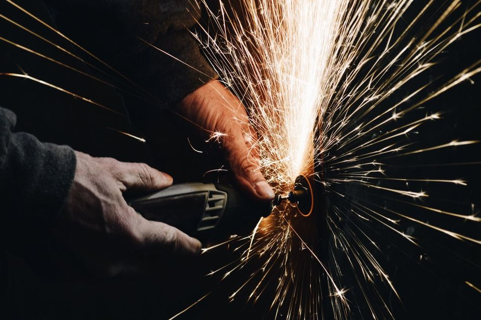 Man using rotary grinder and sparks flying on black background Working Industry Indoors  One Person Metal Human Hand Occupation Skill  Only Men Sparks Men Heat - Temperature Human Body Part One Man Only Metal Industry Manual Worker Motion Close-up Adults Only People Industrial Equipment Industrial Photography Working Hands Industry Industrial