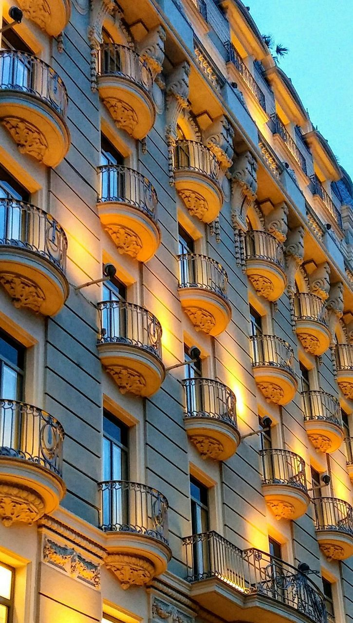 architecture, low angle view, building exterior, built structure, no people, yellow, outdoors, day, city, sky