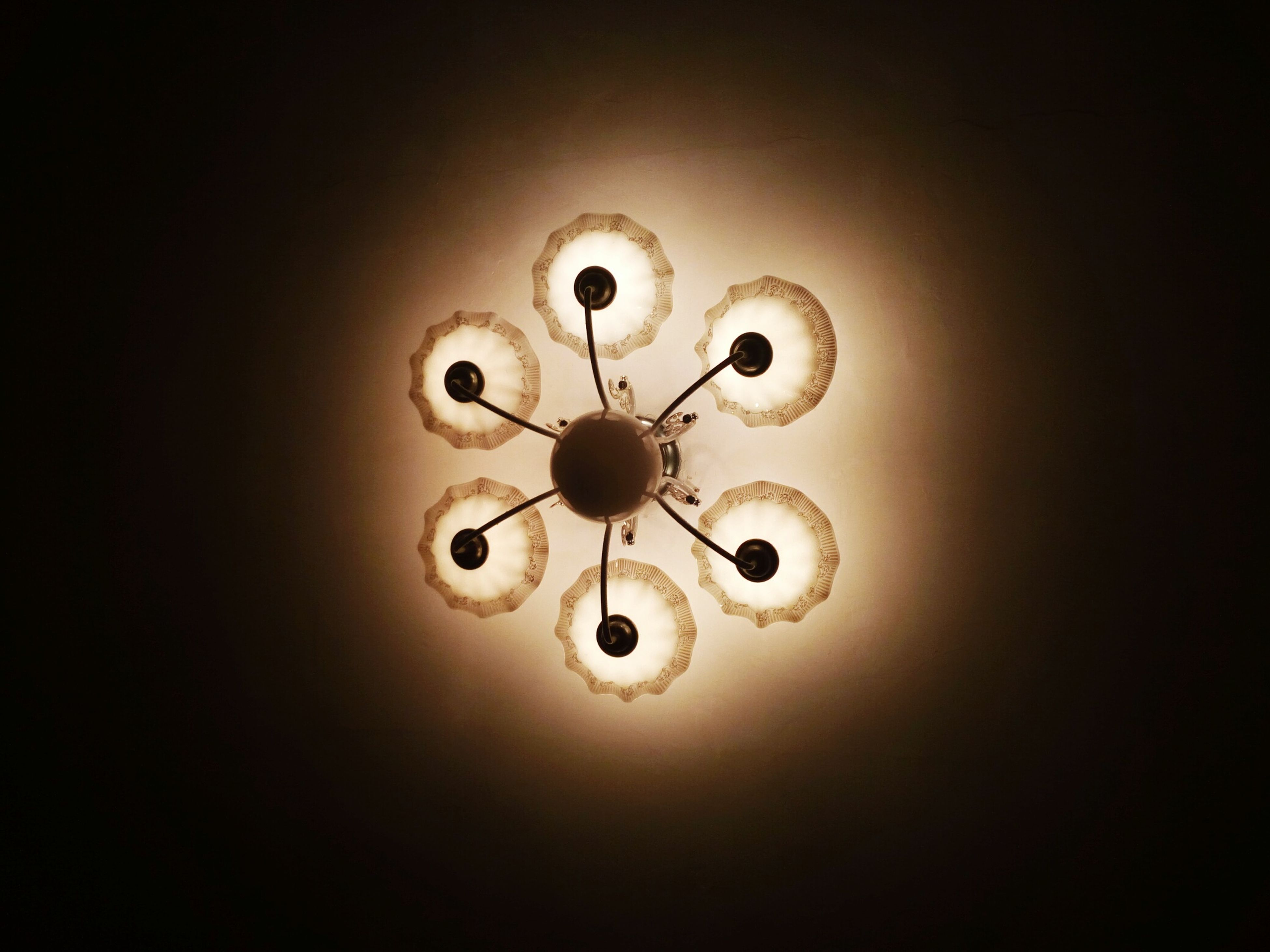 ceiling, lighting equipment, illuminated, indoors, electricity, directly below, low angle view, light - natural phenomenon, chandelier, glowing, geometric shape, modern, electric light, decoration, circle, no people, architectural feature, darkroom, ceiling light